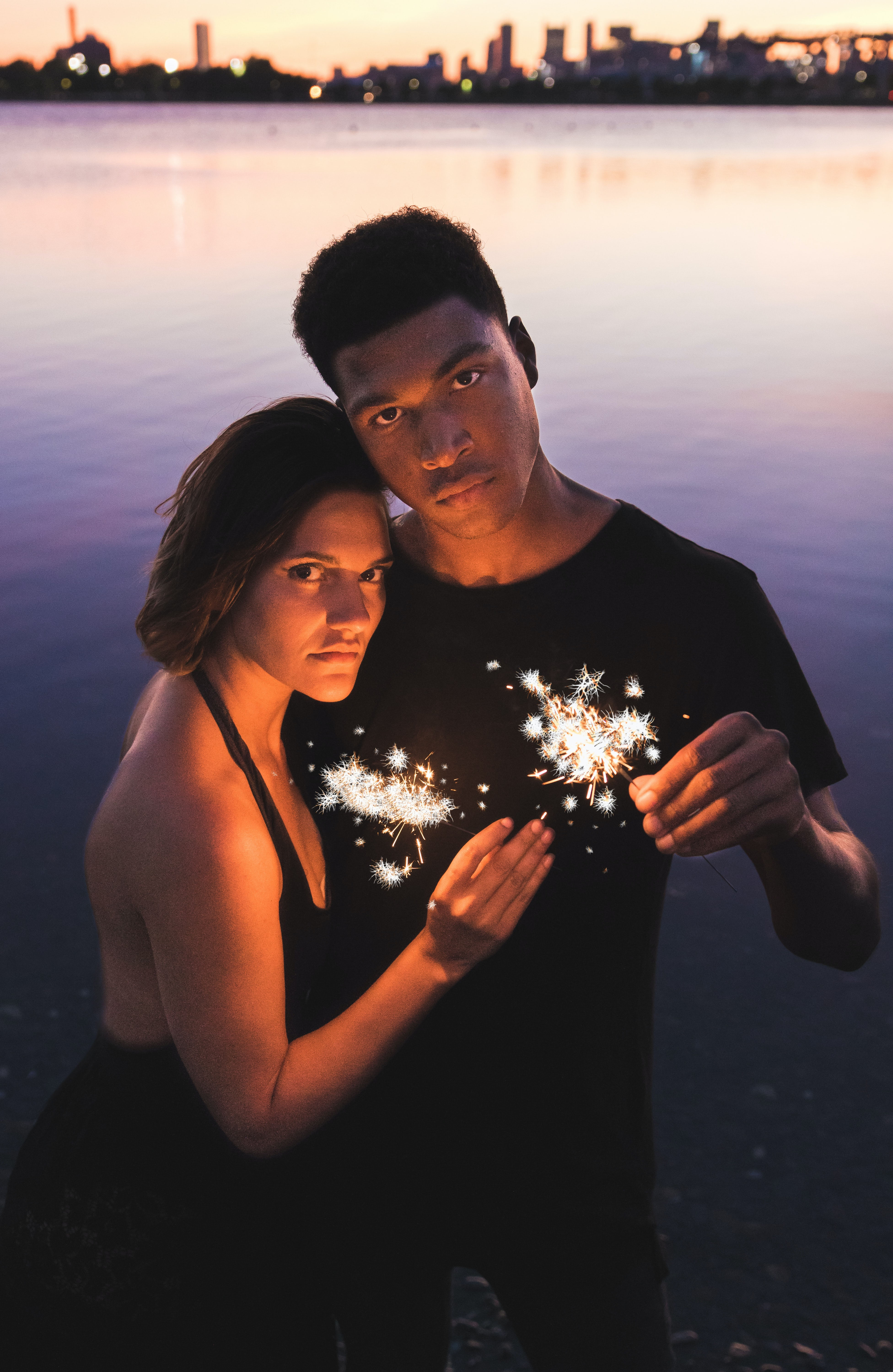 couple holding sparklers standing near body of water at dusk