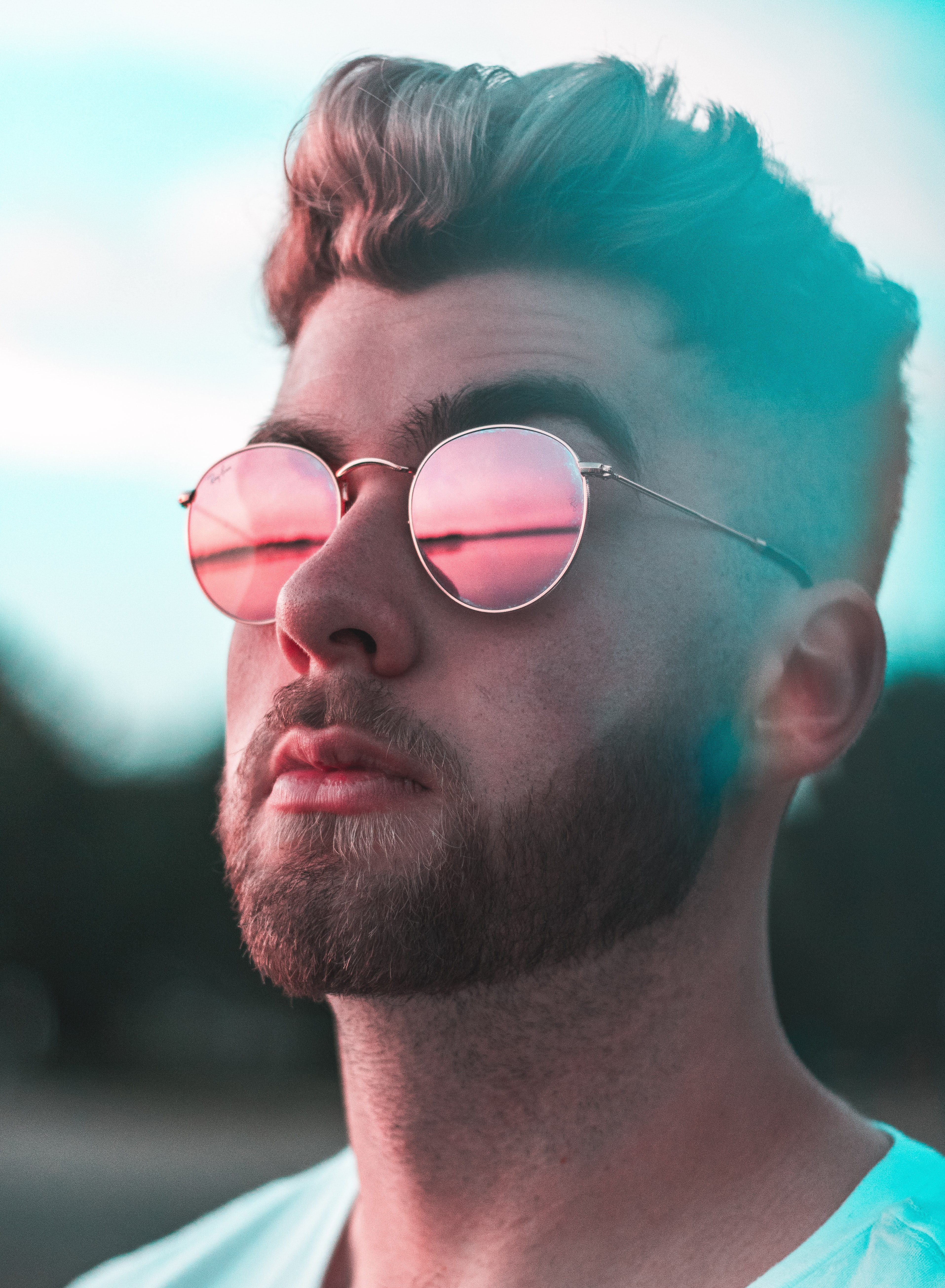 A bearded man wearing reflective sunglasses looks into the distance outdoors