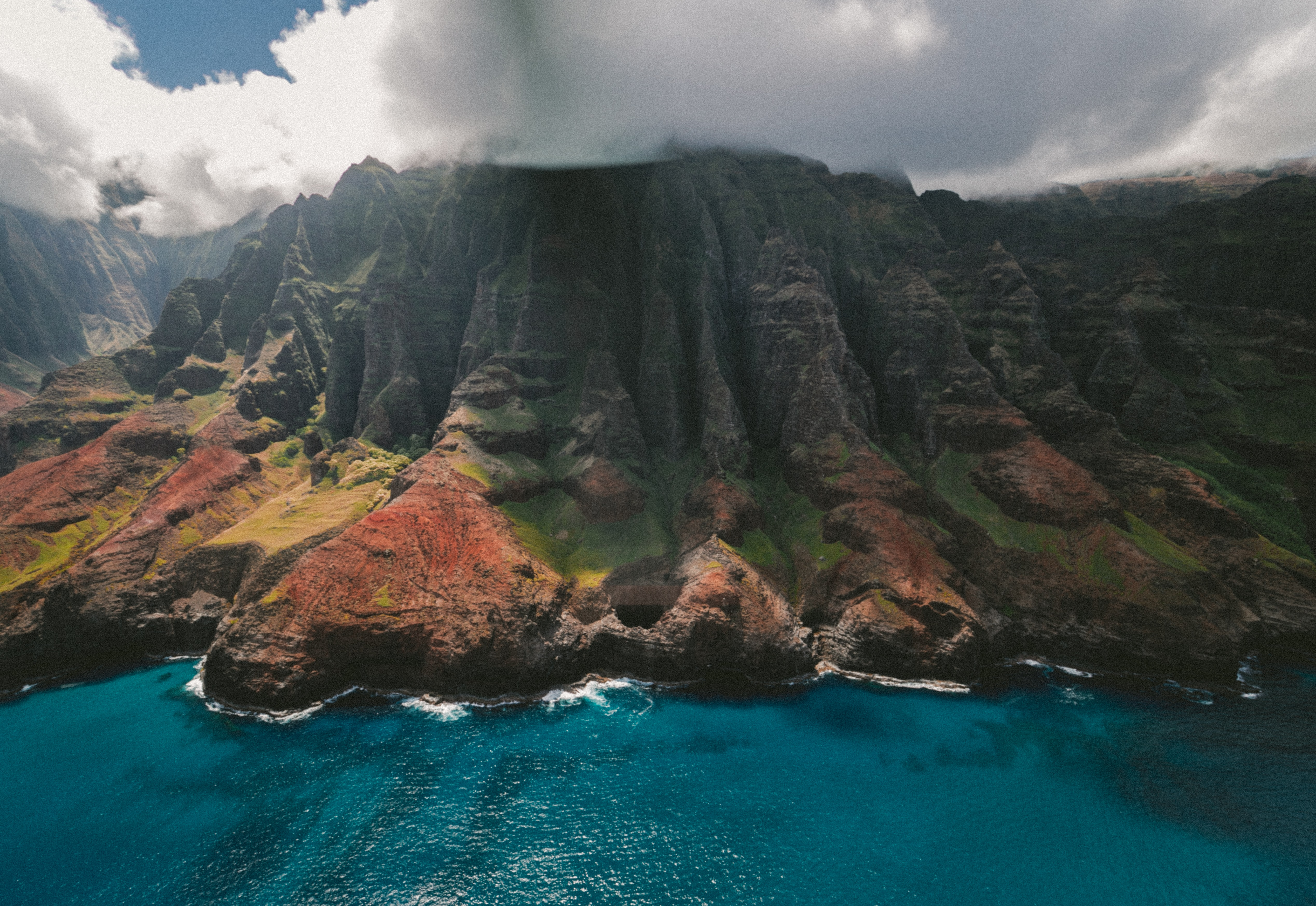 A drone shot of a colorful cliff with green moss and red rocks over azure water