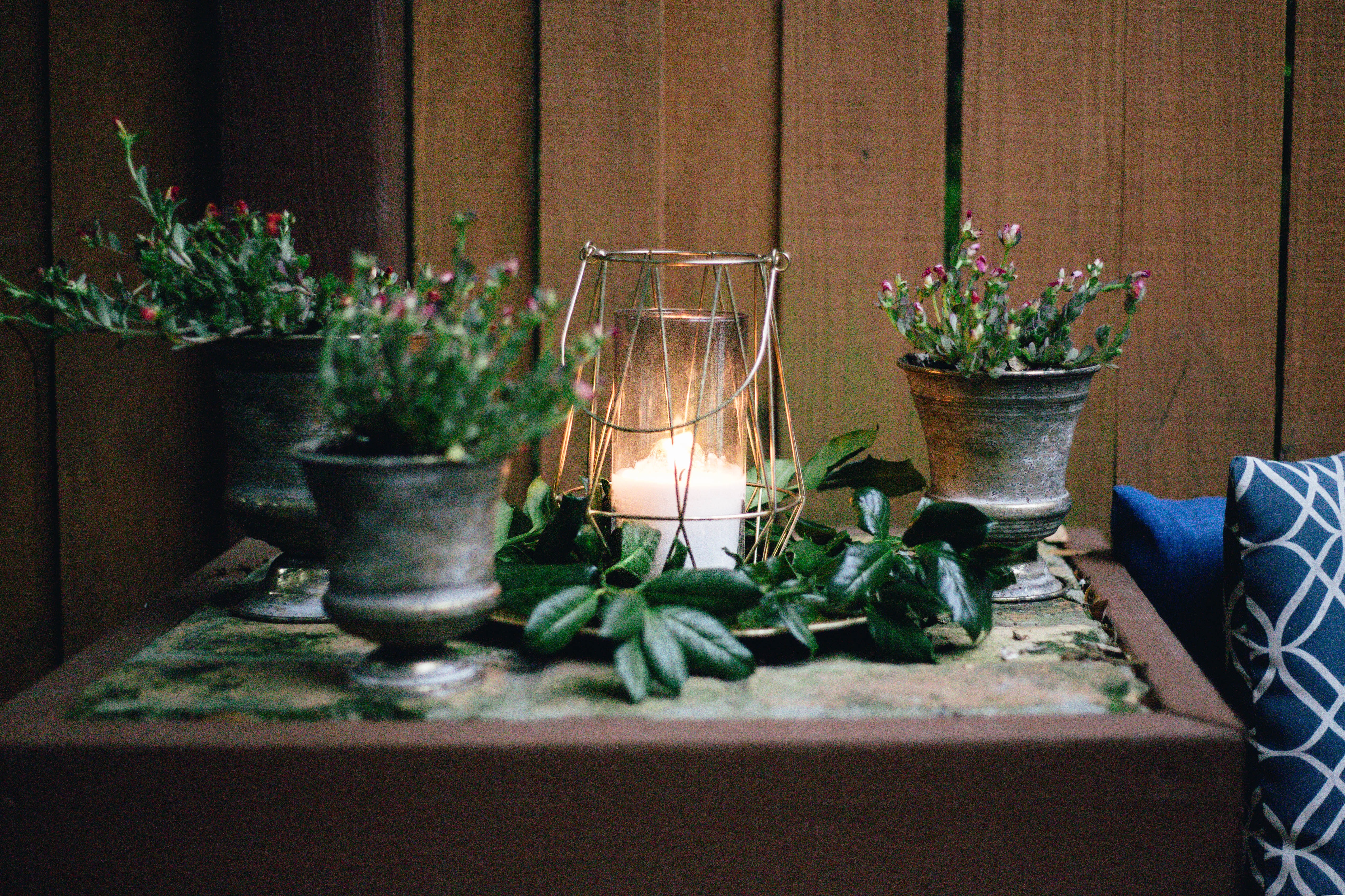 lighted candle on table beside pots