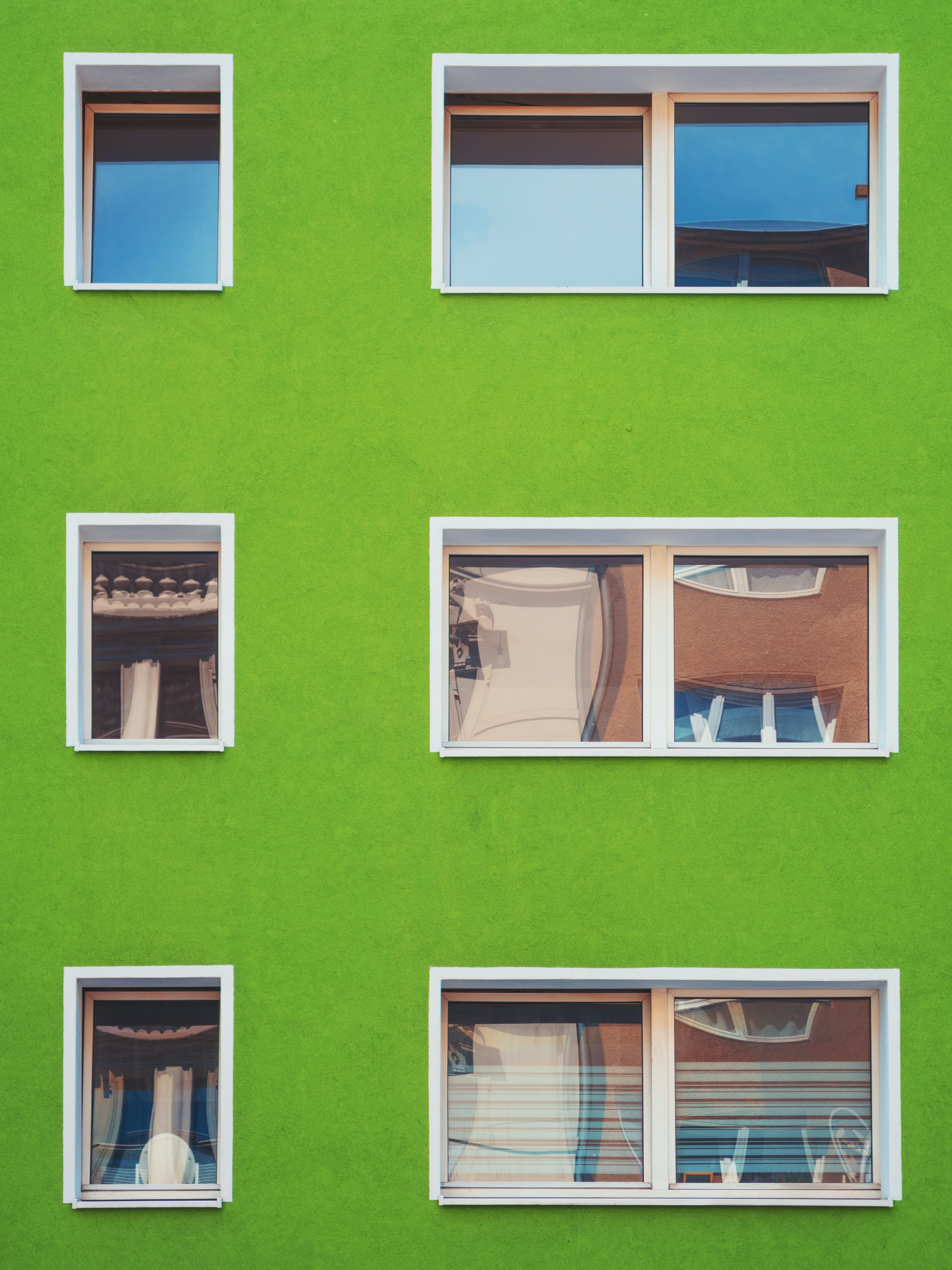 Small windows in a green wall of a residential building in Cologne