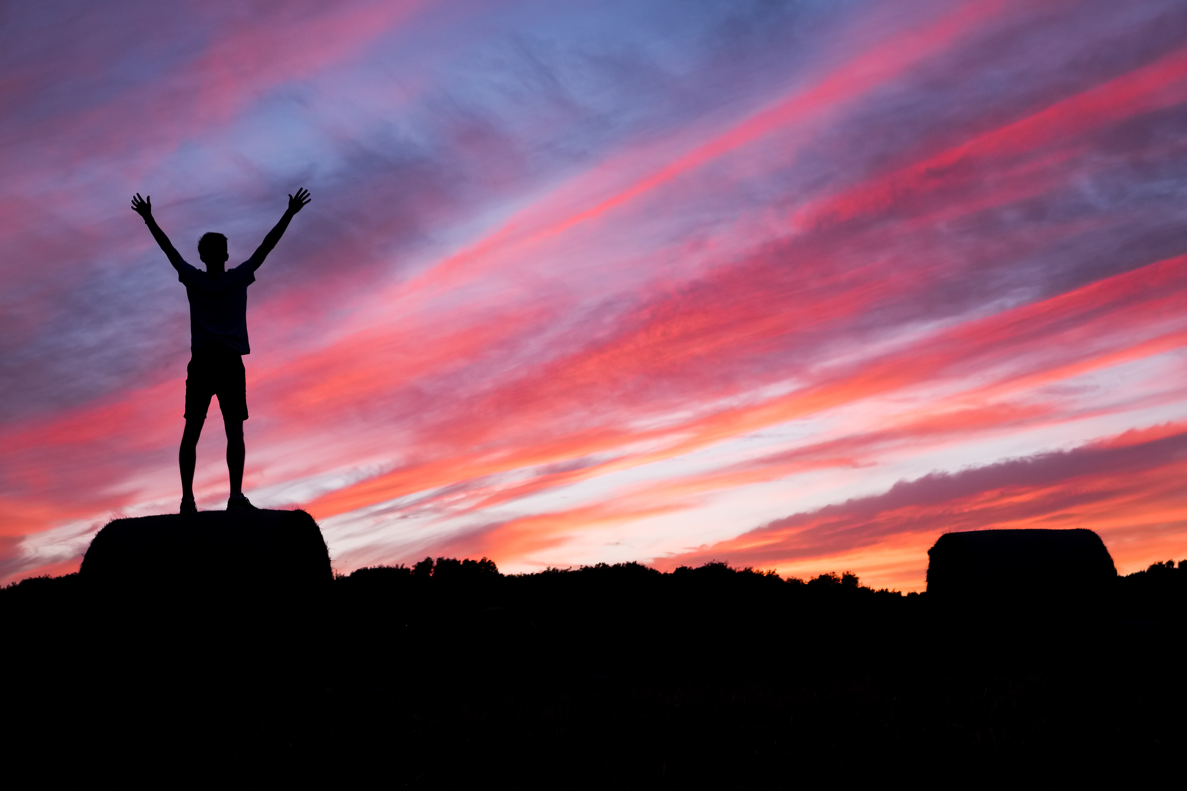 A silhouette of a man lifting up his hands while while standing on a rock at sunrise
