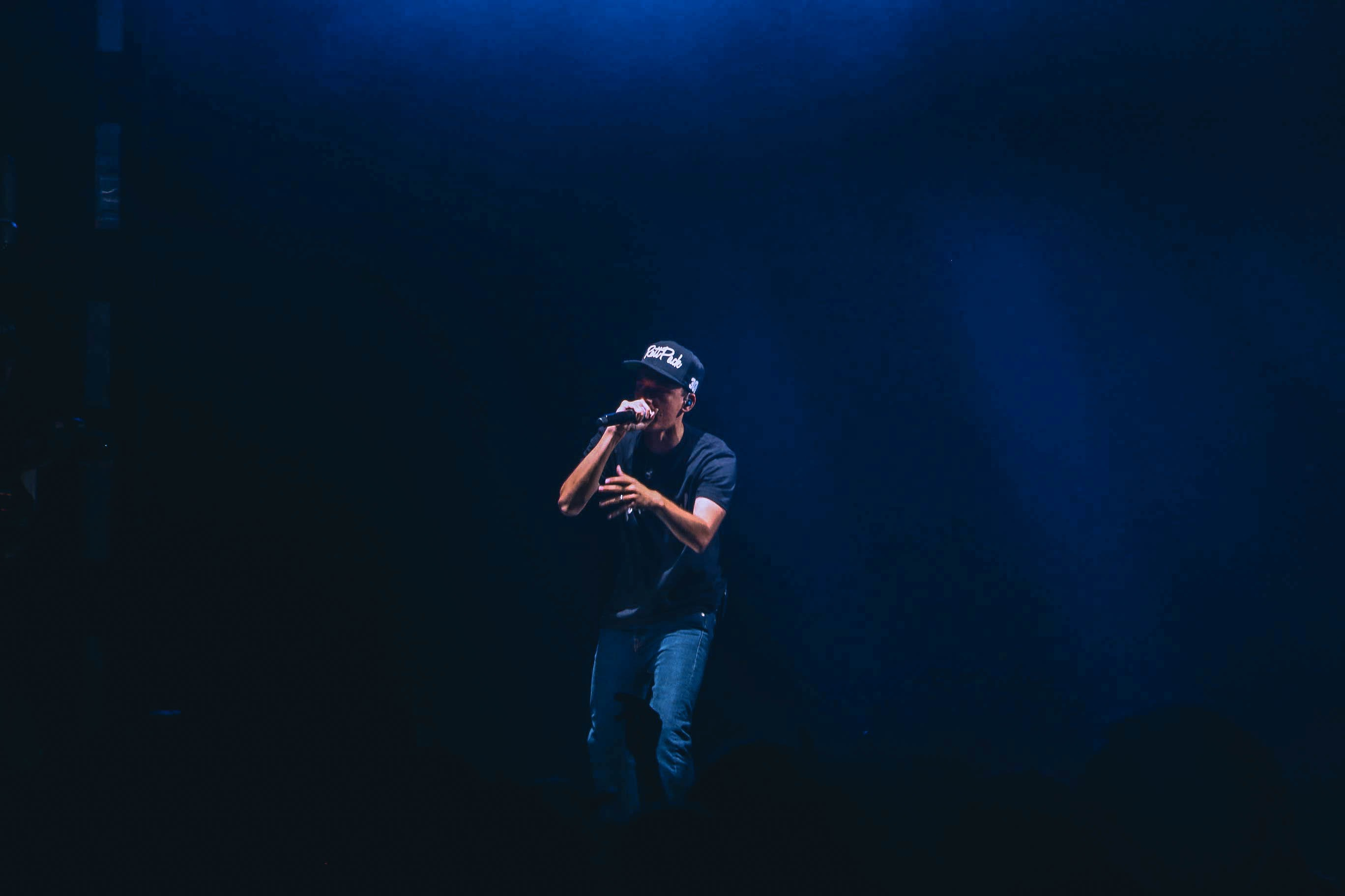 A rapper performing on stage wearing a cap and holding a microphone under blue spotlight