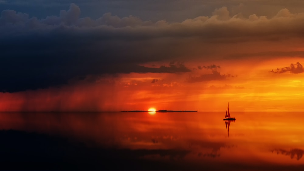 silhouette of sailboat on body of water