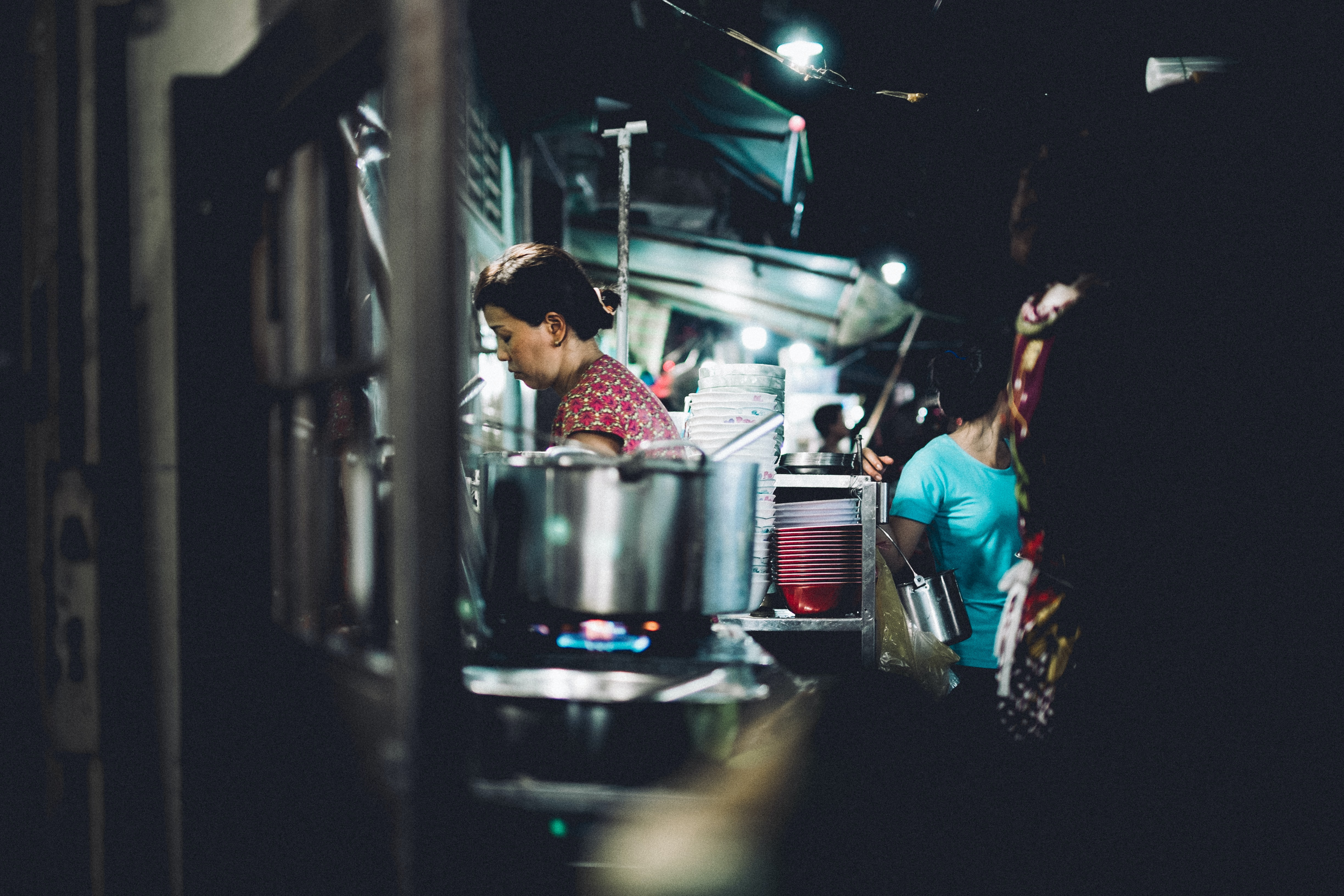 A woman cooks food at street food night market in Ho Chi Minh City