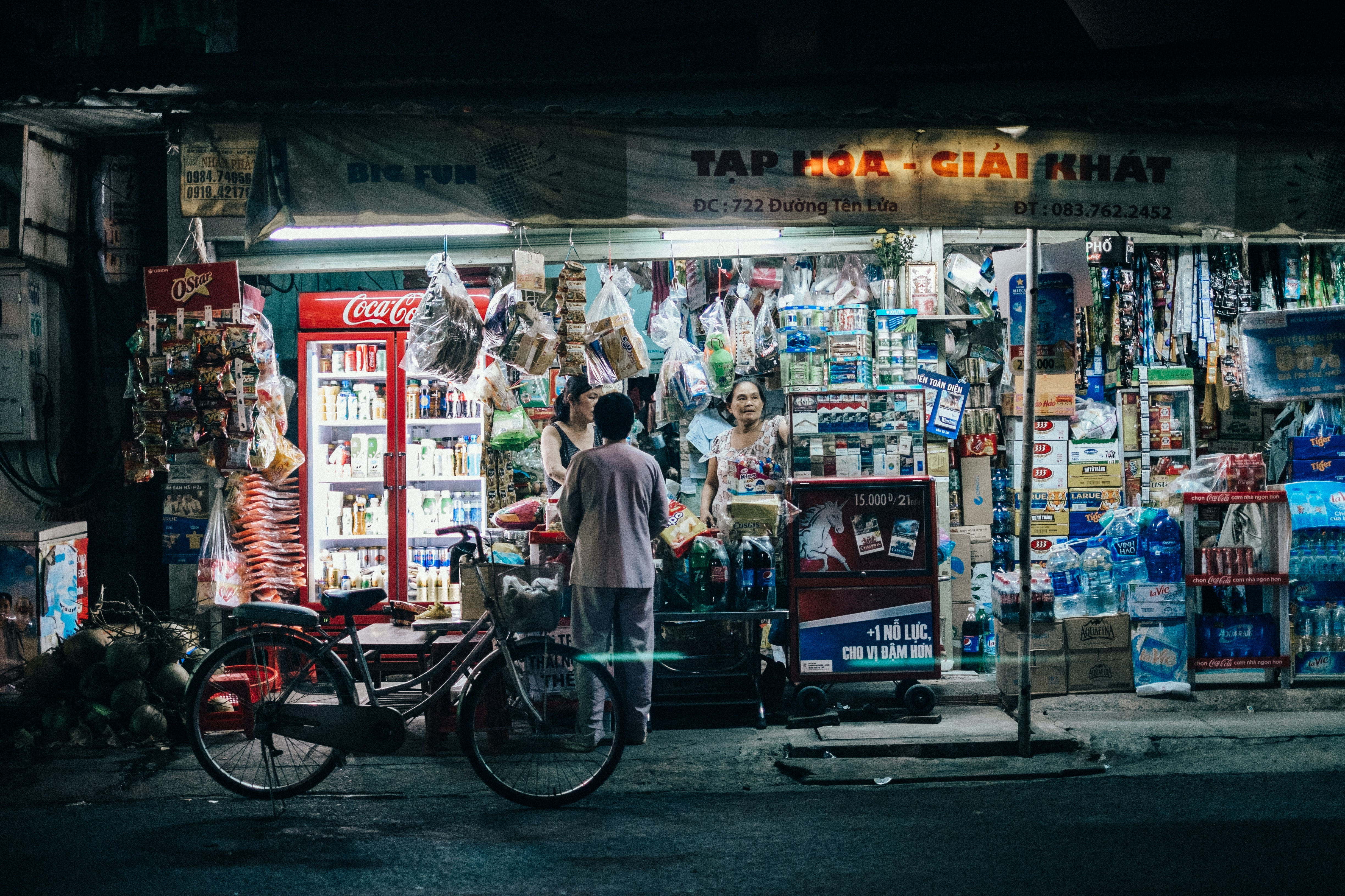 A person with a bike shopping at a street stall in Ho Chi Minh City at night