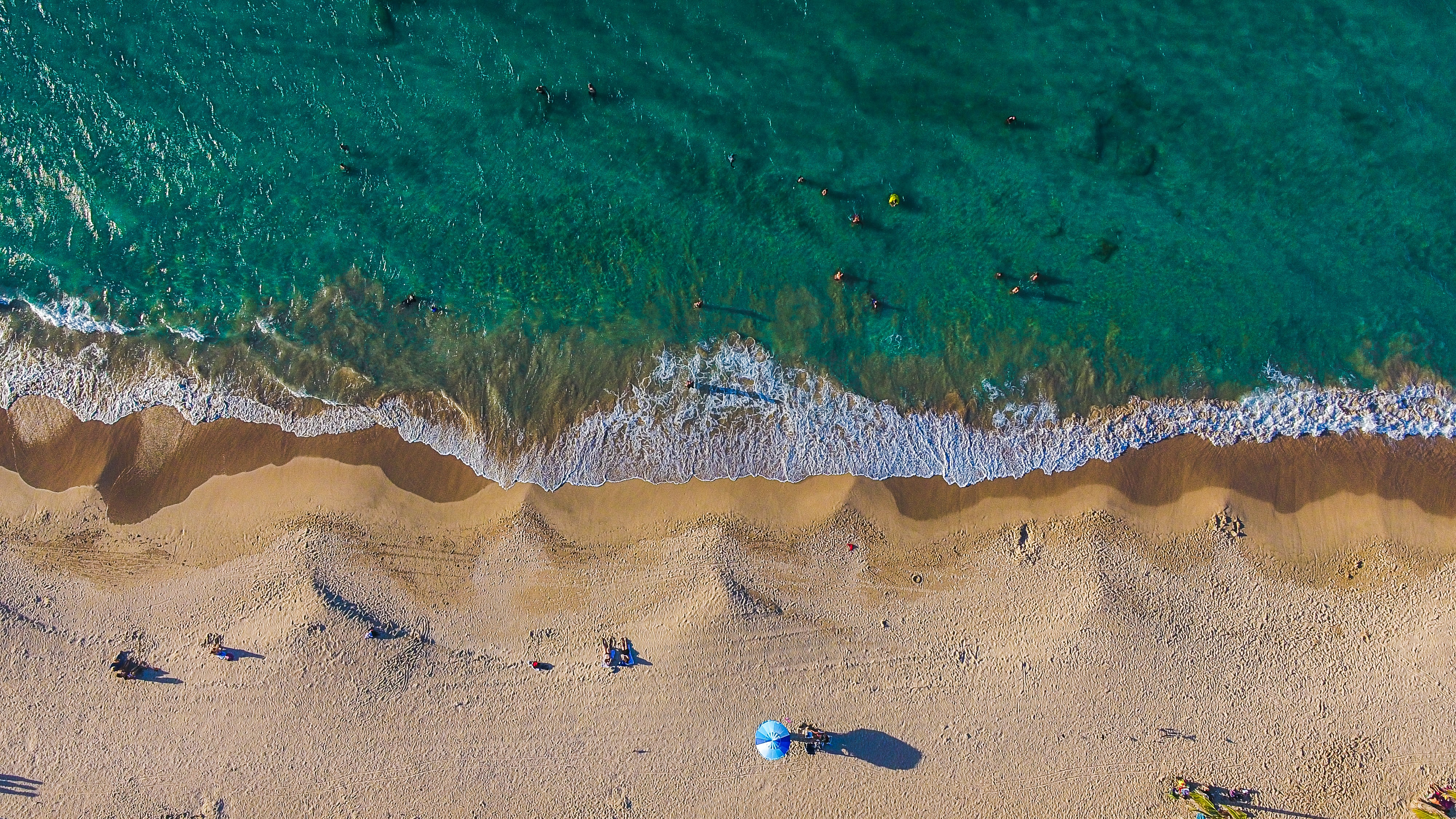 aerial photography of person walking near seashore during daytime