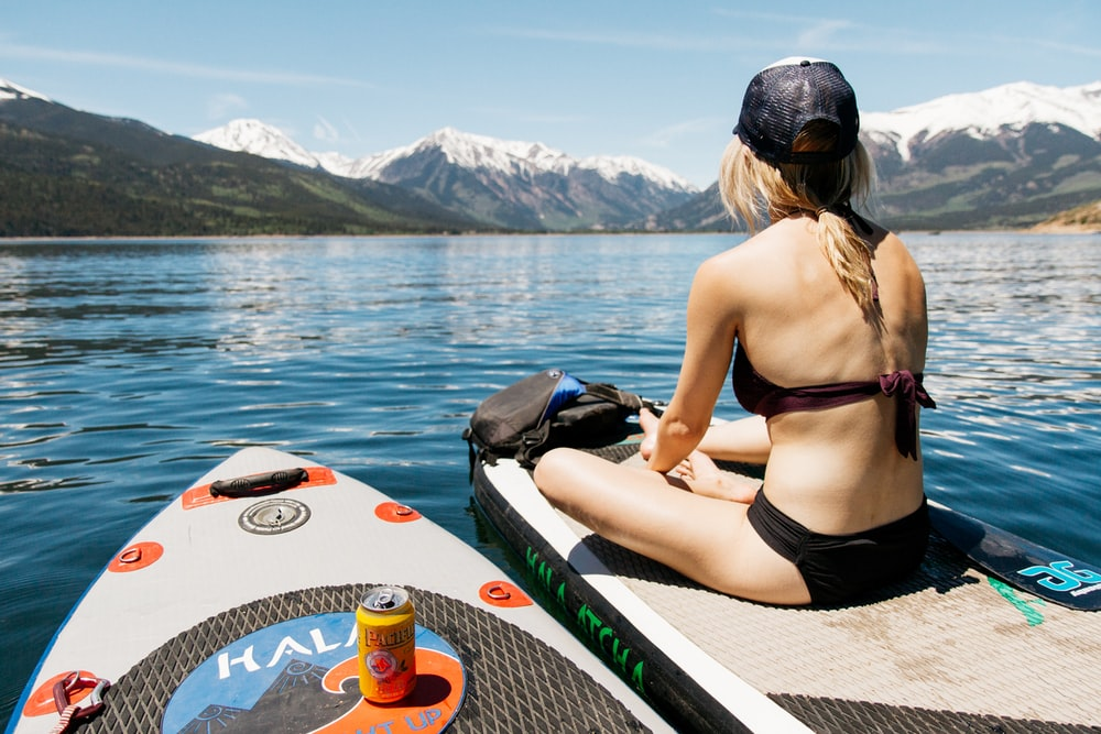 woman sitting on boat while floating on calm water at daytime