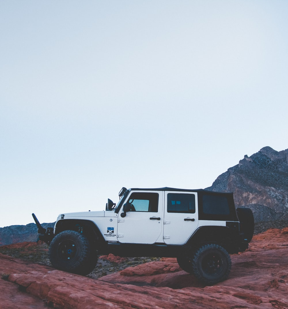 white and black SUV on brown rocks