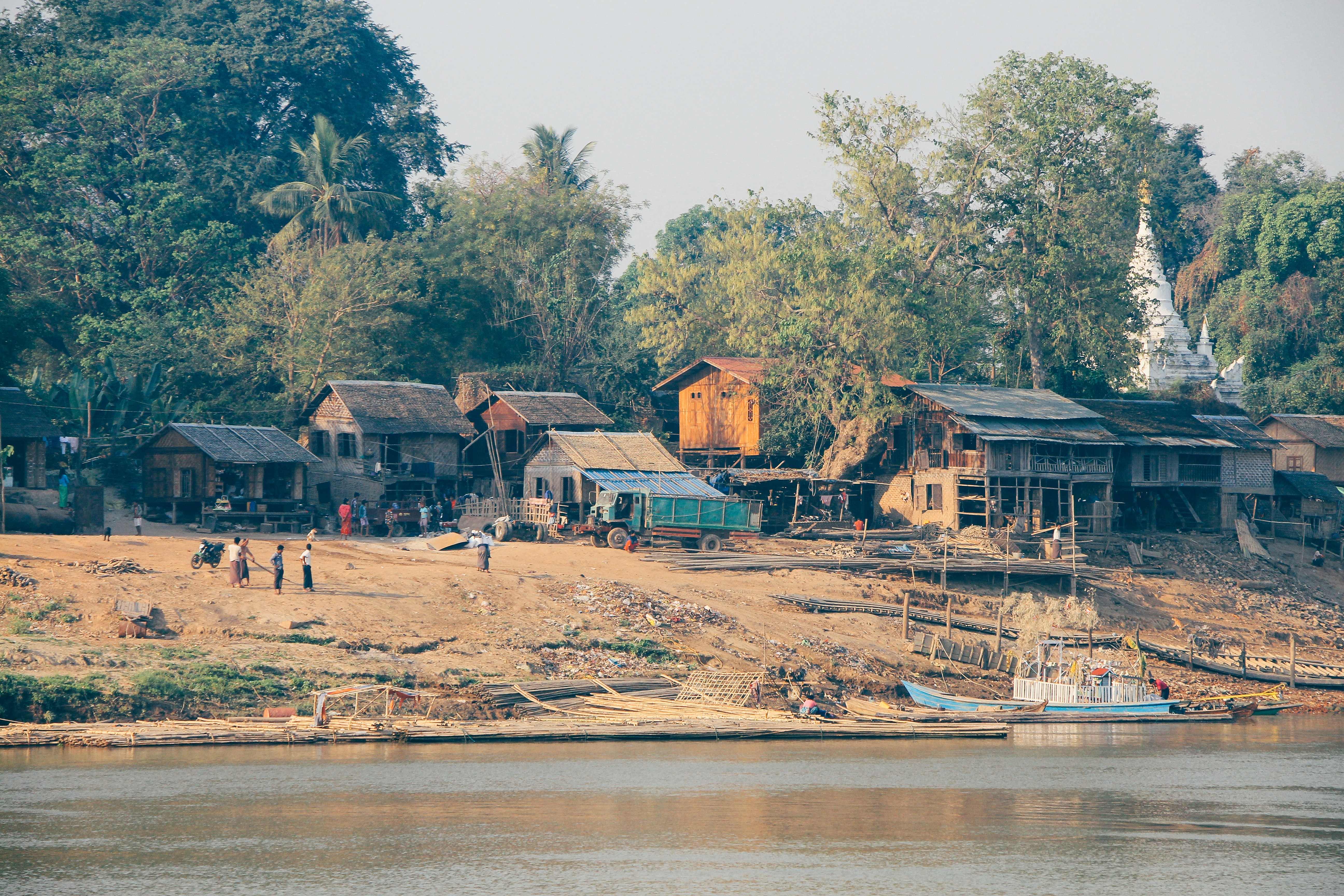 A small village with wooden houses, trees, few people and a river next to it in old began.