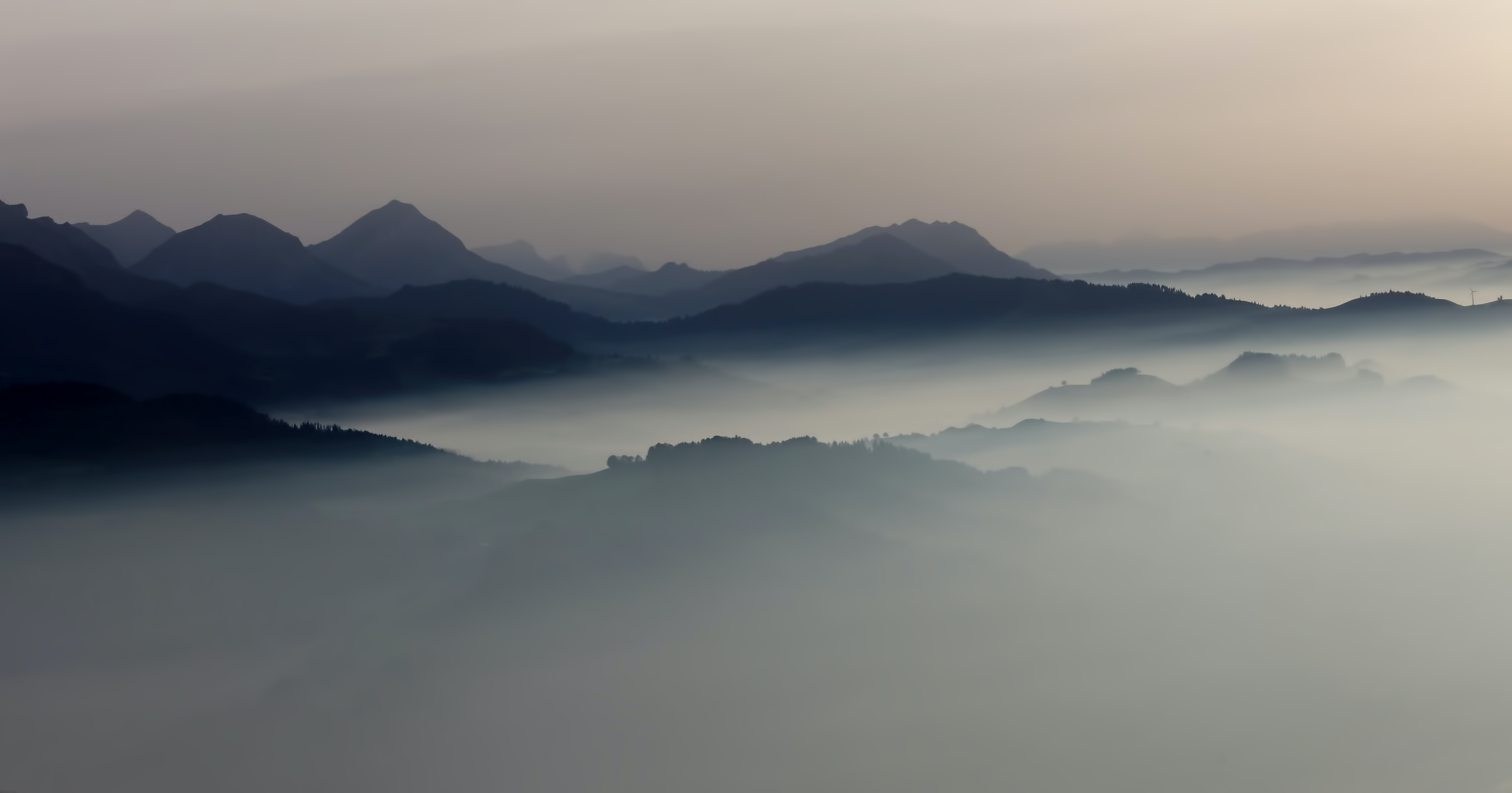 Dark silhouettes of mountain peaks emerge from the mist in Lucerne