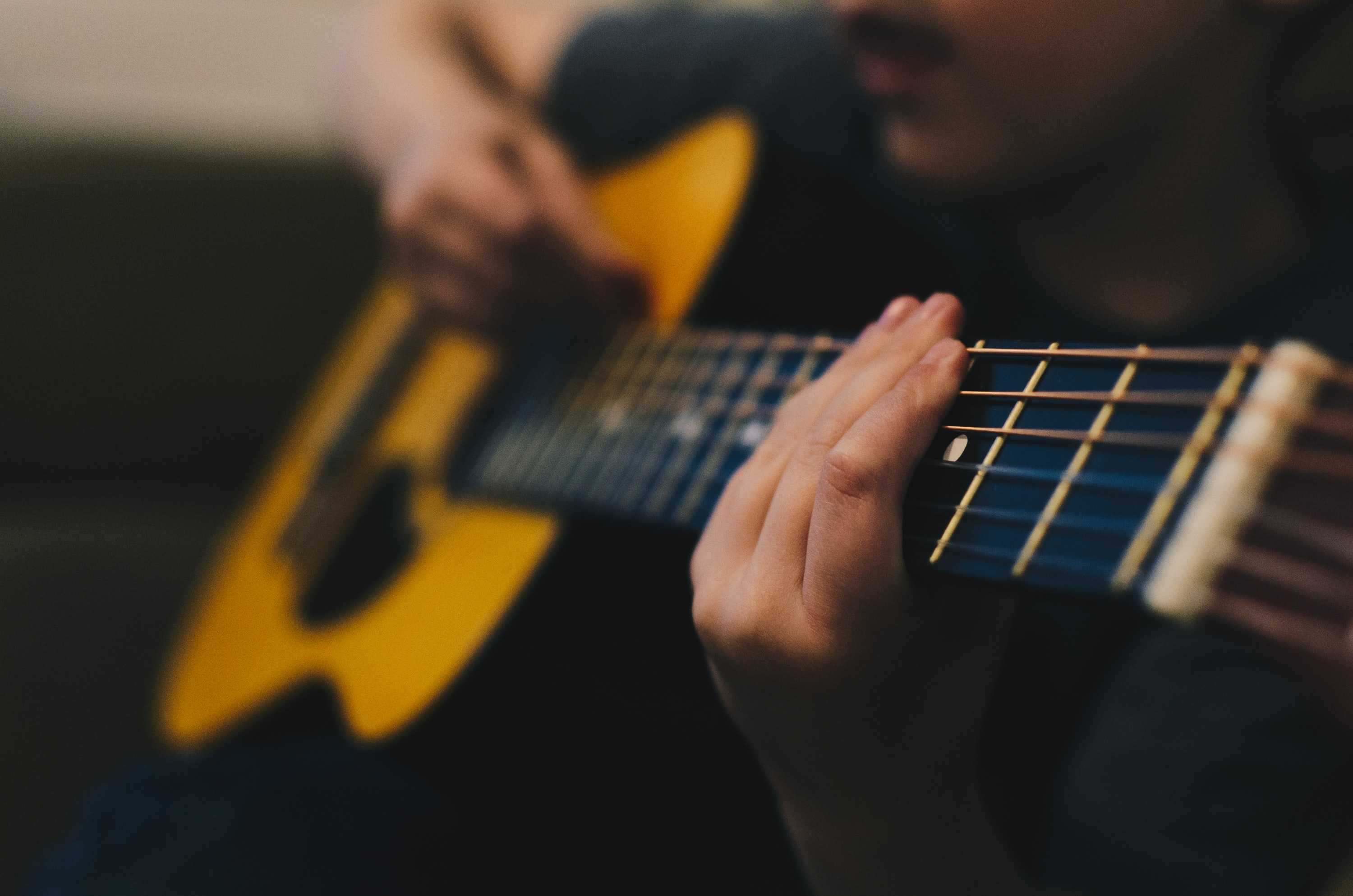 A fuzzy shot of a man playing an acoustic guitar