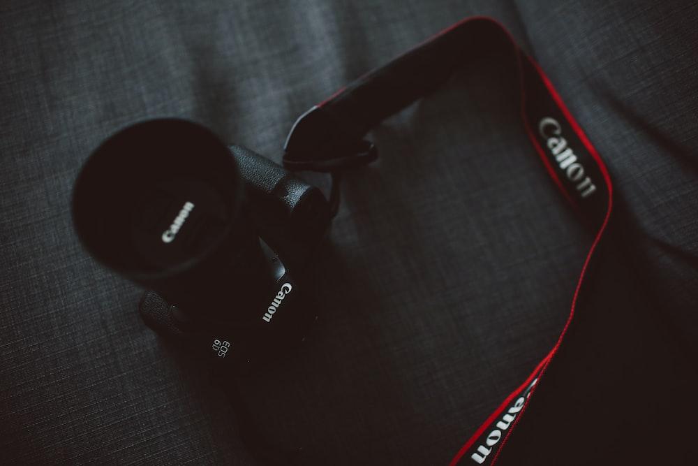 black Canon EOS DSLR camera on gray textile