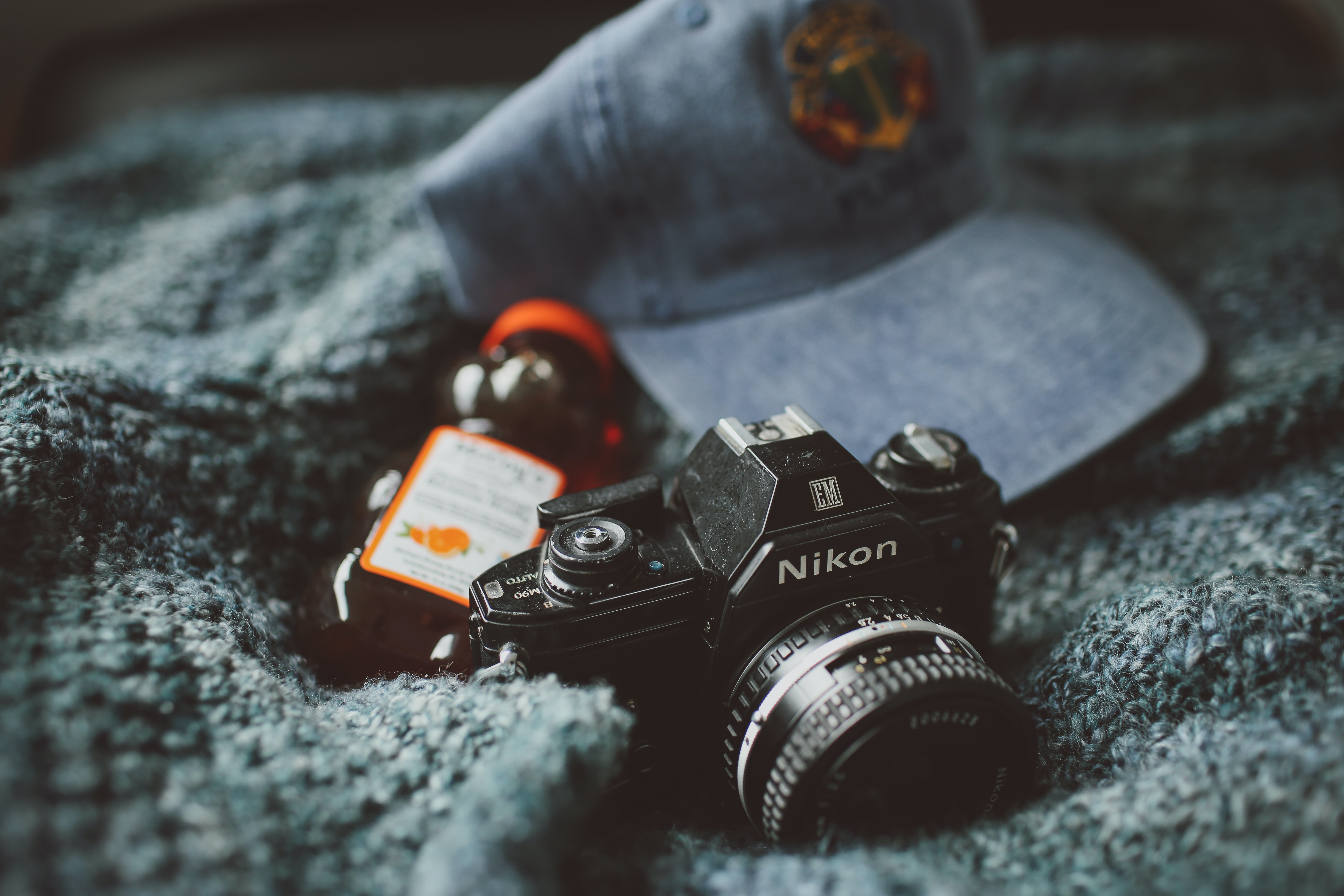 A vintage Nikon camera with its lens cover beside a bottle of honey and a blue cap on a gray blanket
