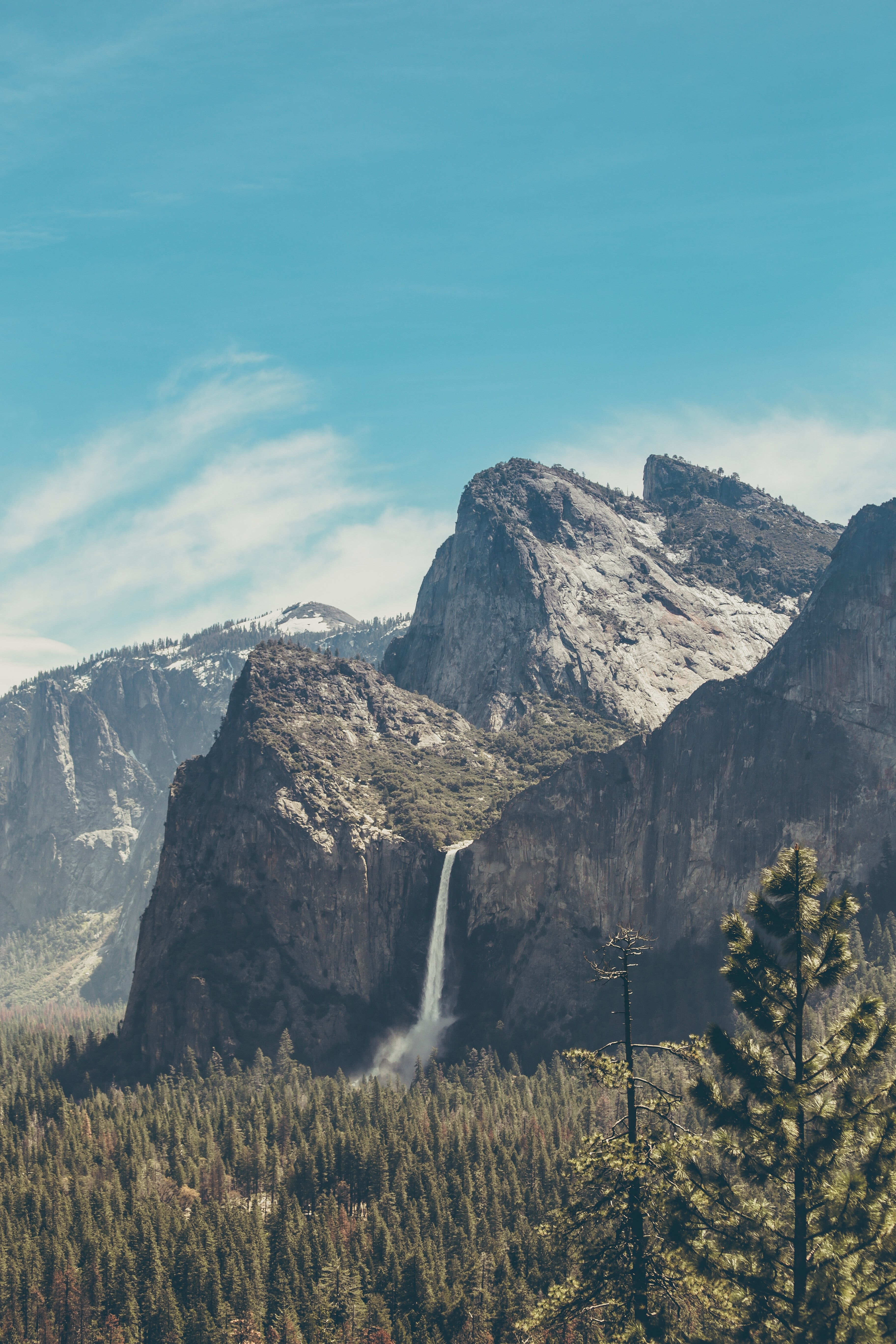 A magnificent landscape with a waterfall tumbling down a rocky face overlooking an evergreen forest
