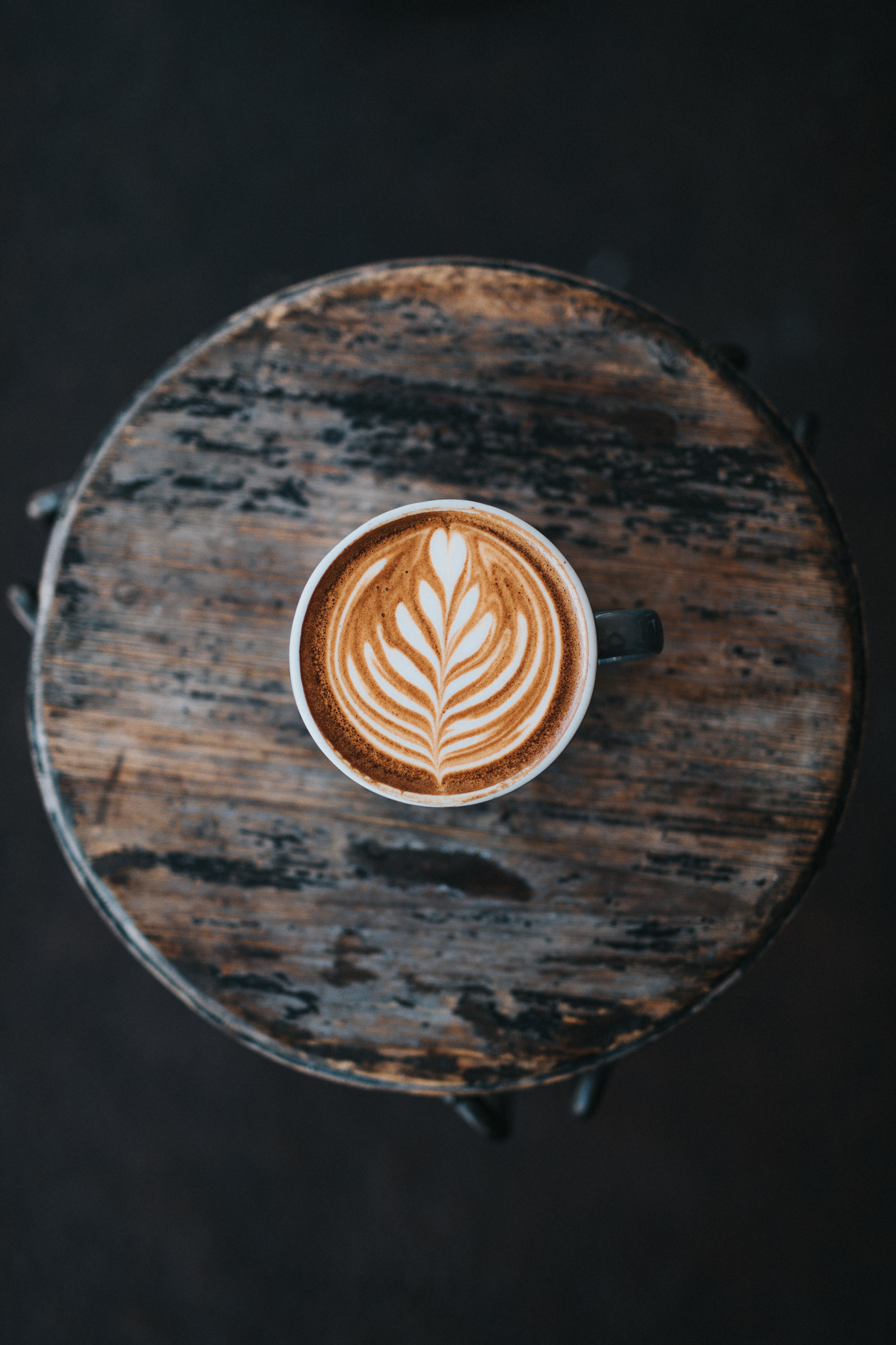 Coffee latte art viewed from above in a cup on the wooden table at Two Guns Espresso