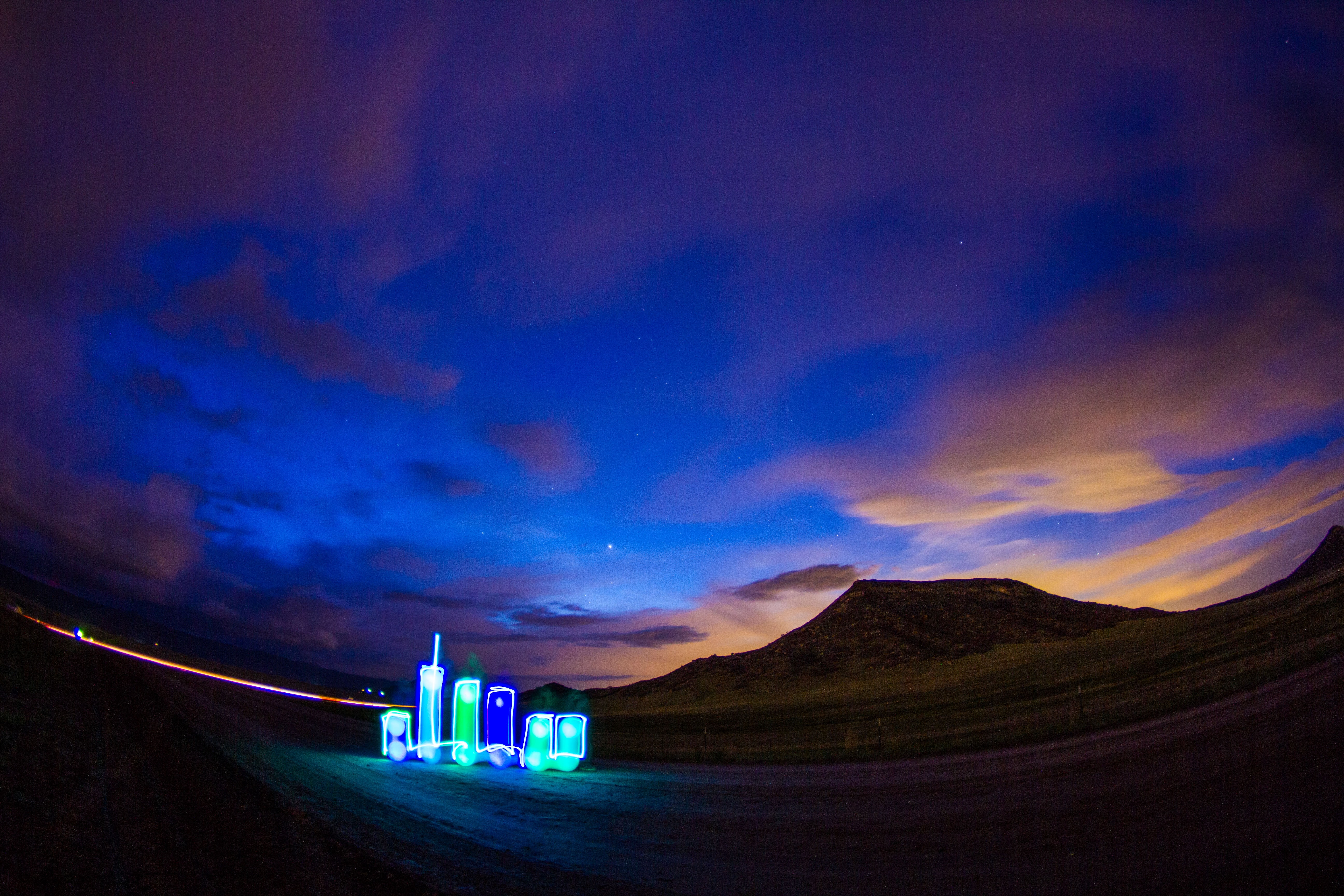 Long exposure and wide angle landscape in Denver at sunset with a highway and lights.