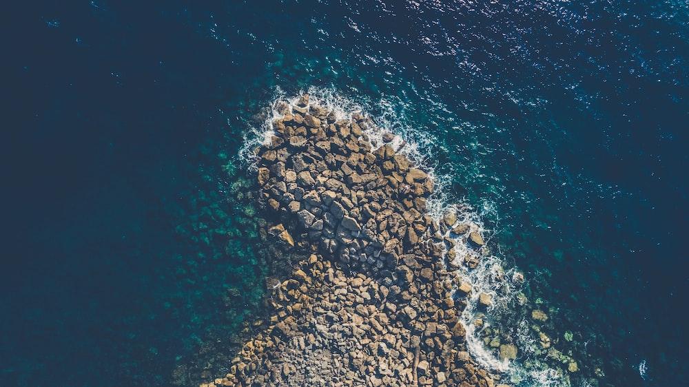 aerial view photography of brown rocks beside ocean