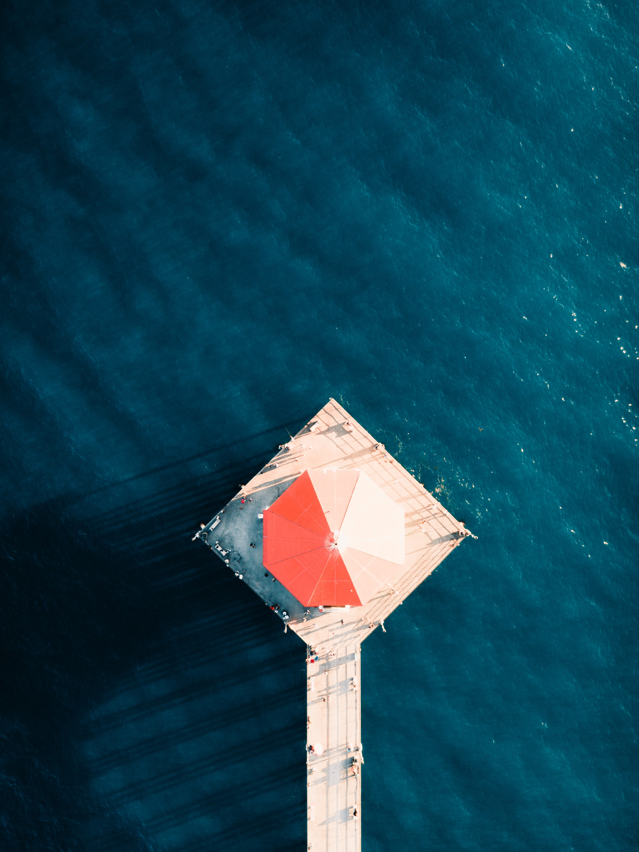 white dock with umbrella on body of water