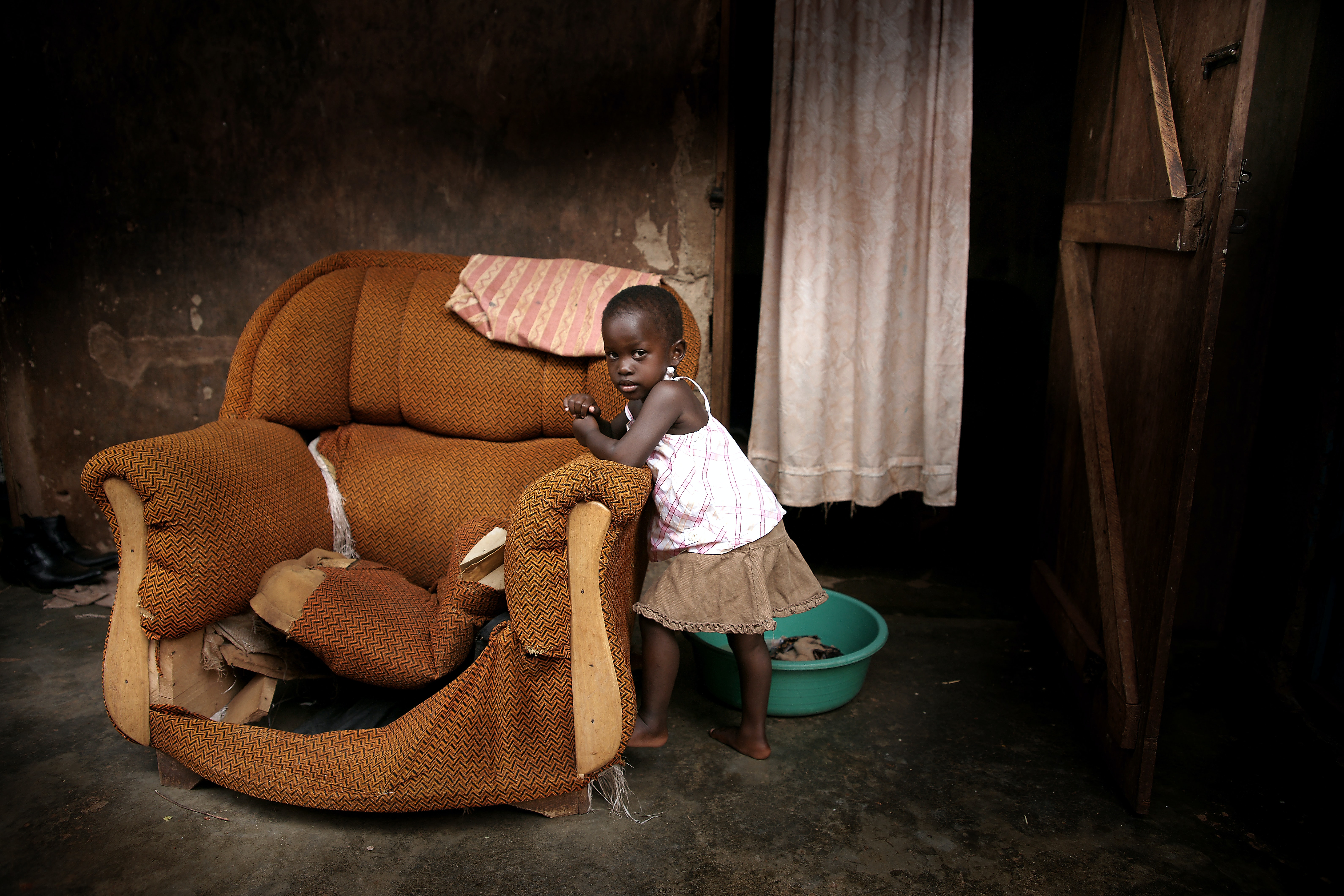 A little girl leaning against an old, broken couch that has no cushions in a house in Kampala