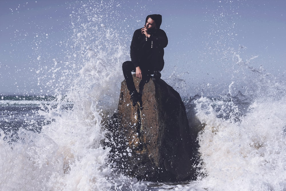 man in black jacket sitting on rock formation in the middle of water