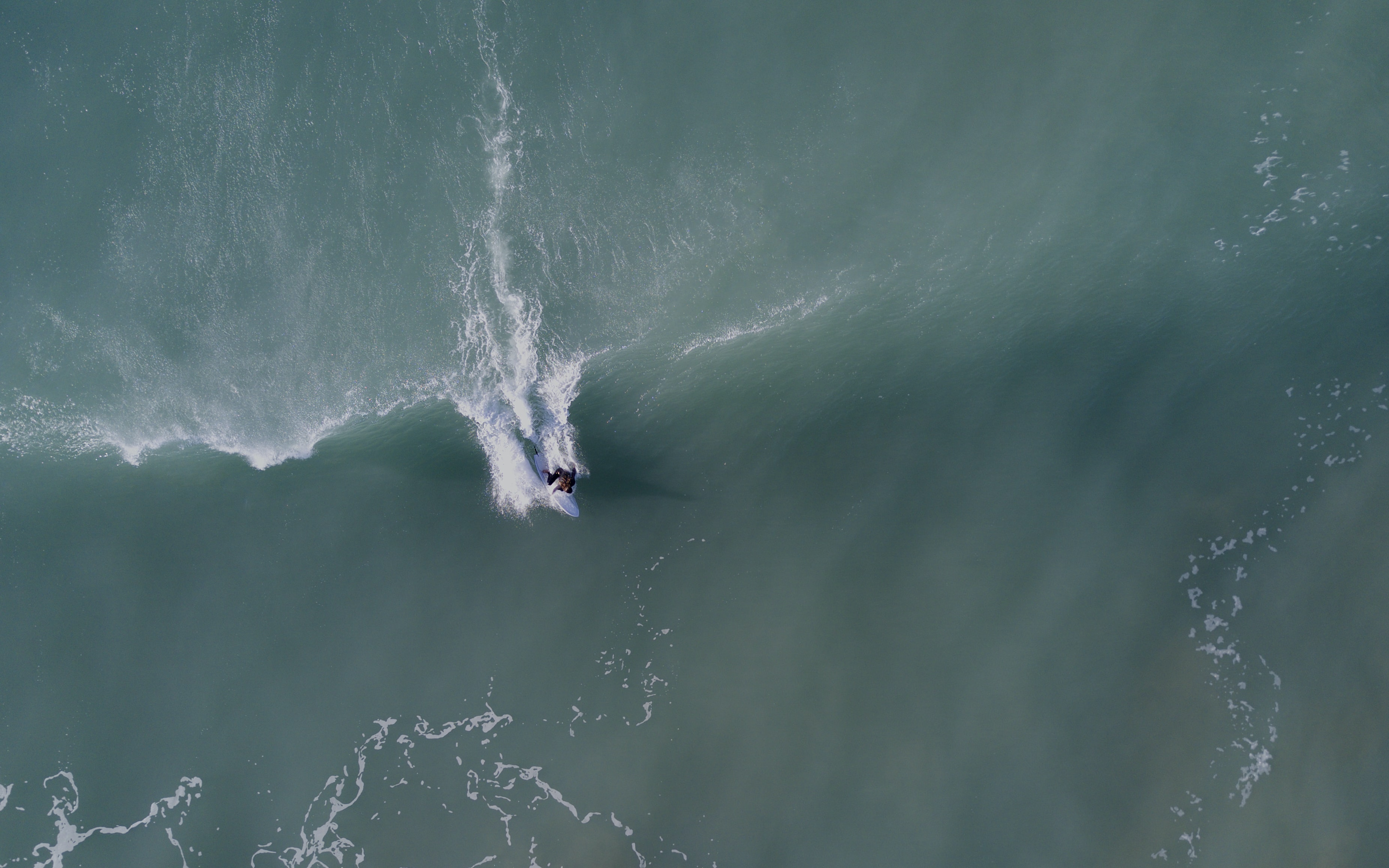 A drone shot of a surfer riding a wave in Gisborne, New Zealand
