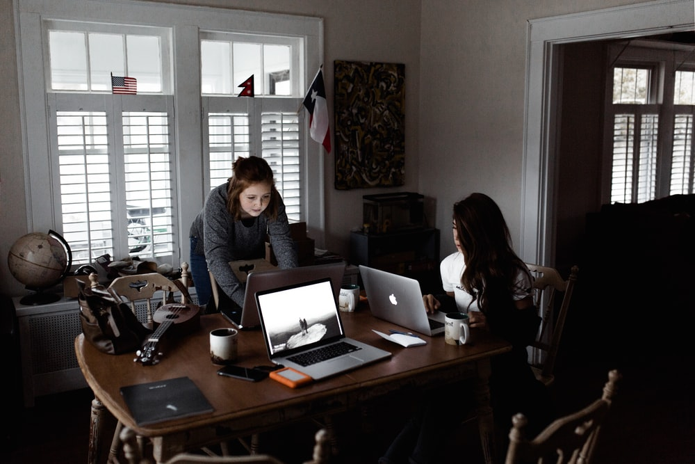 women using laptop on brown wooden table