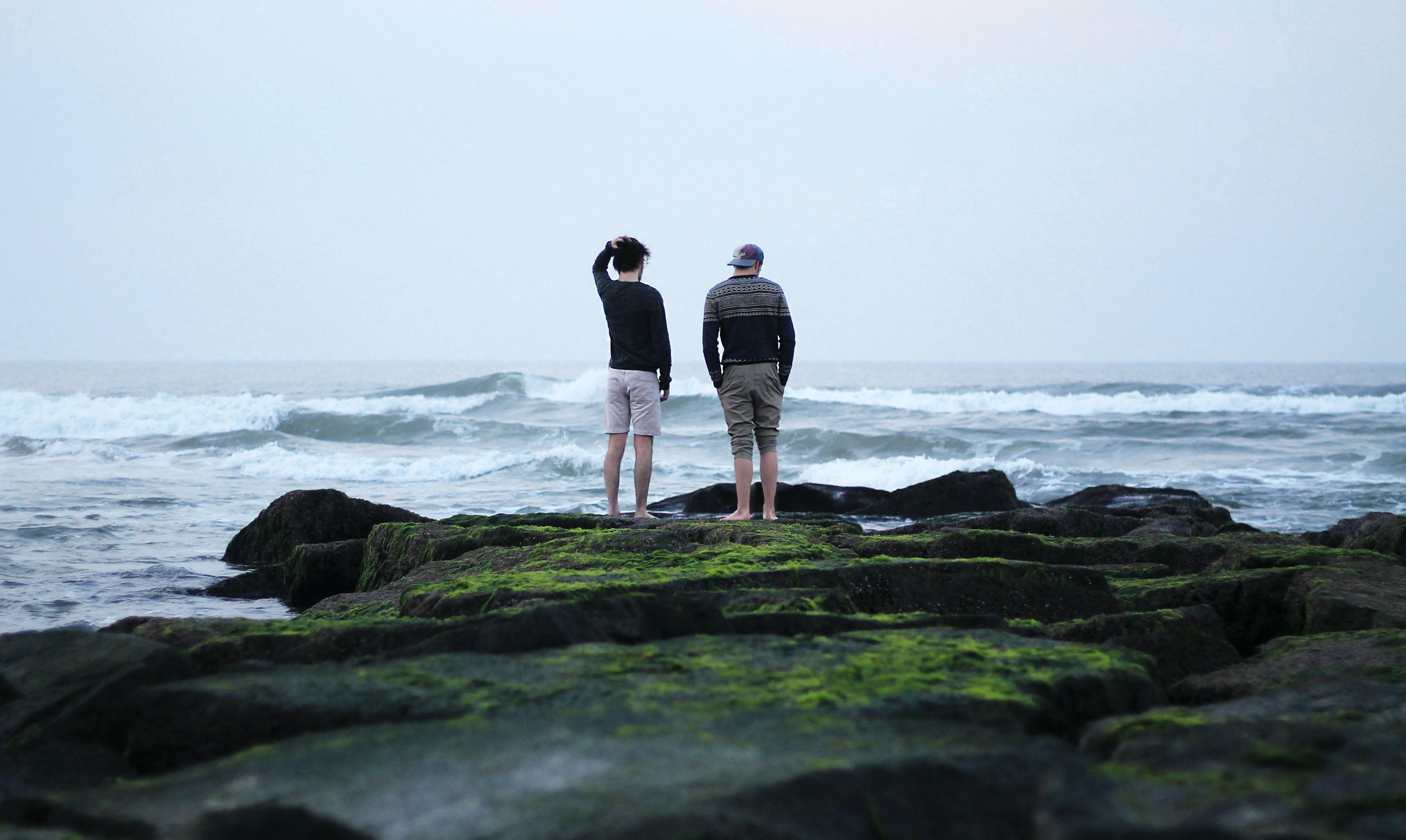 Two men standing on coastal rocks, looking out to sea