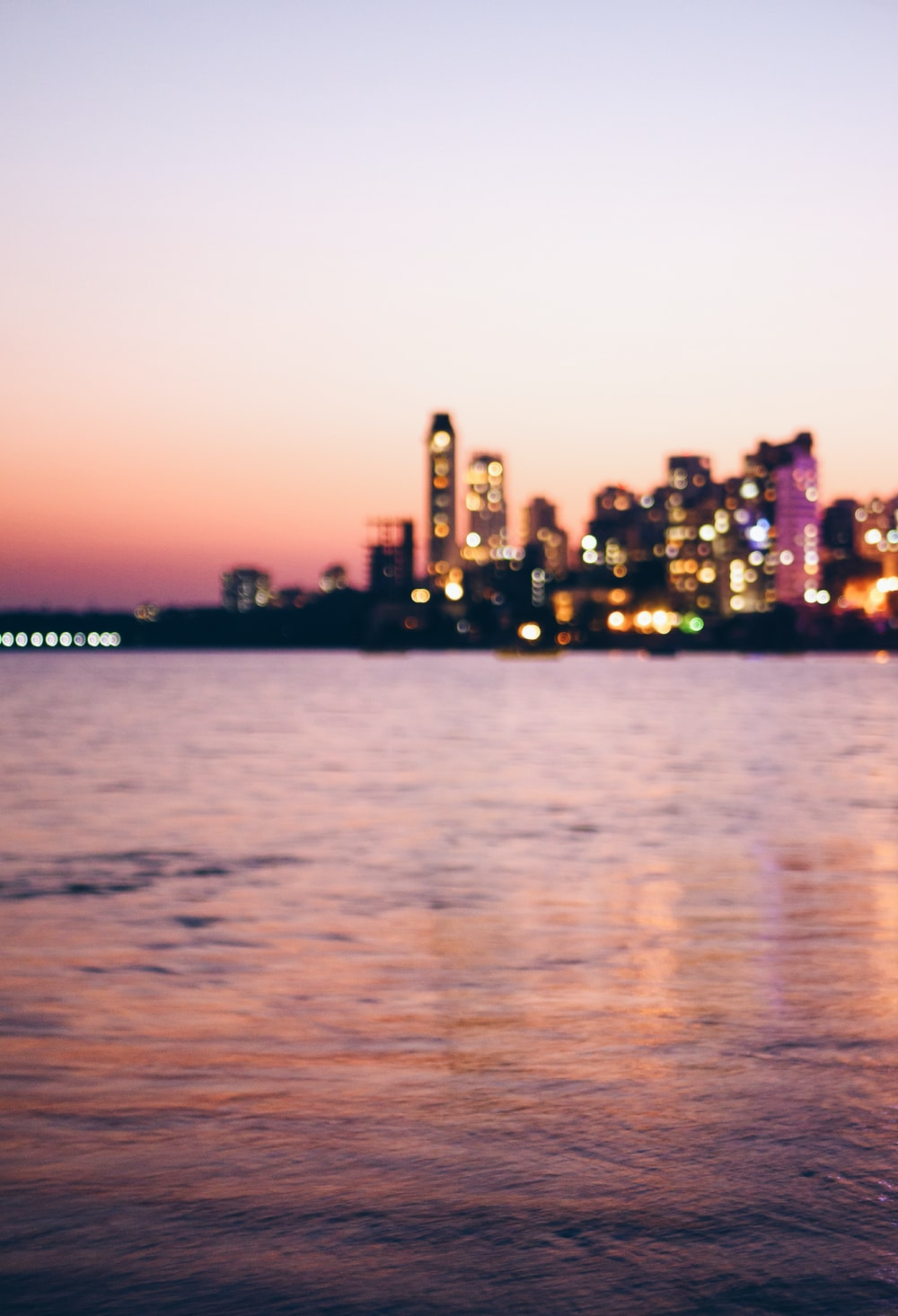 landscape photography of lighted buildings beside body of water