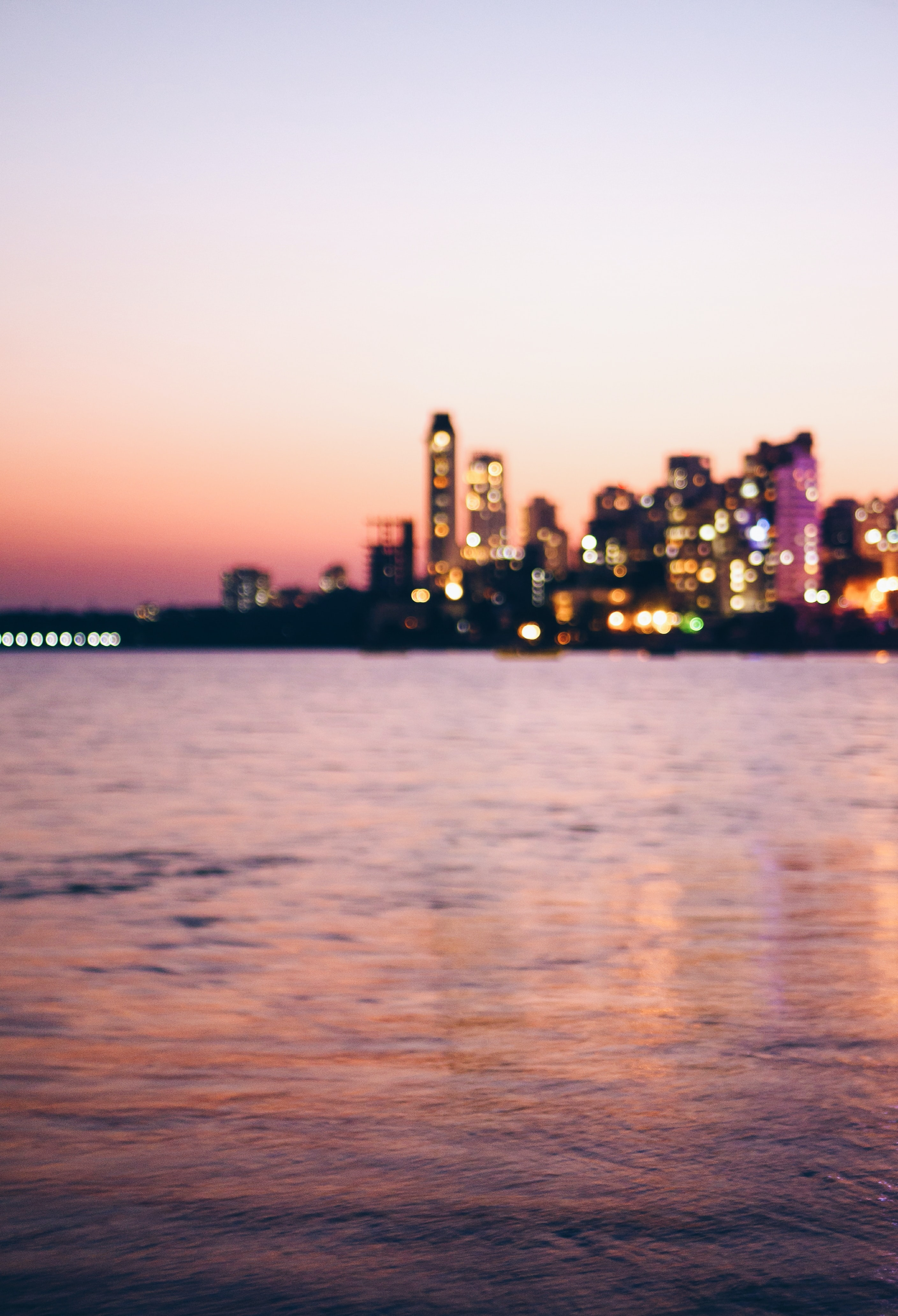 A blurry city skyline seen from a body of water on an evening