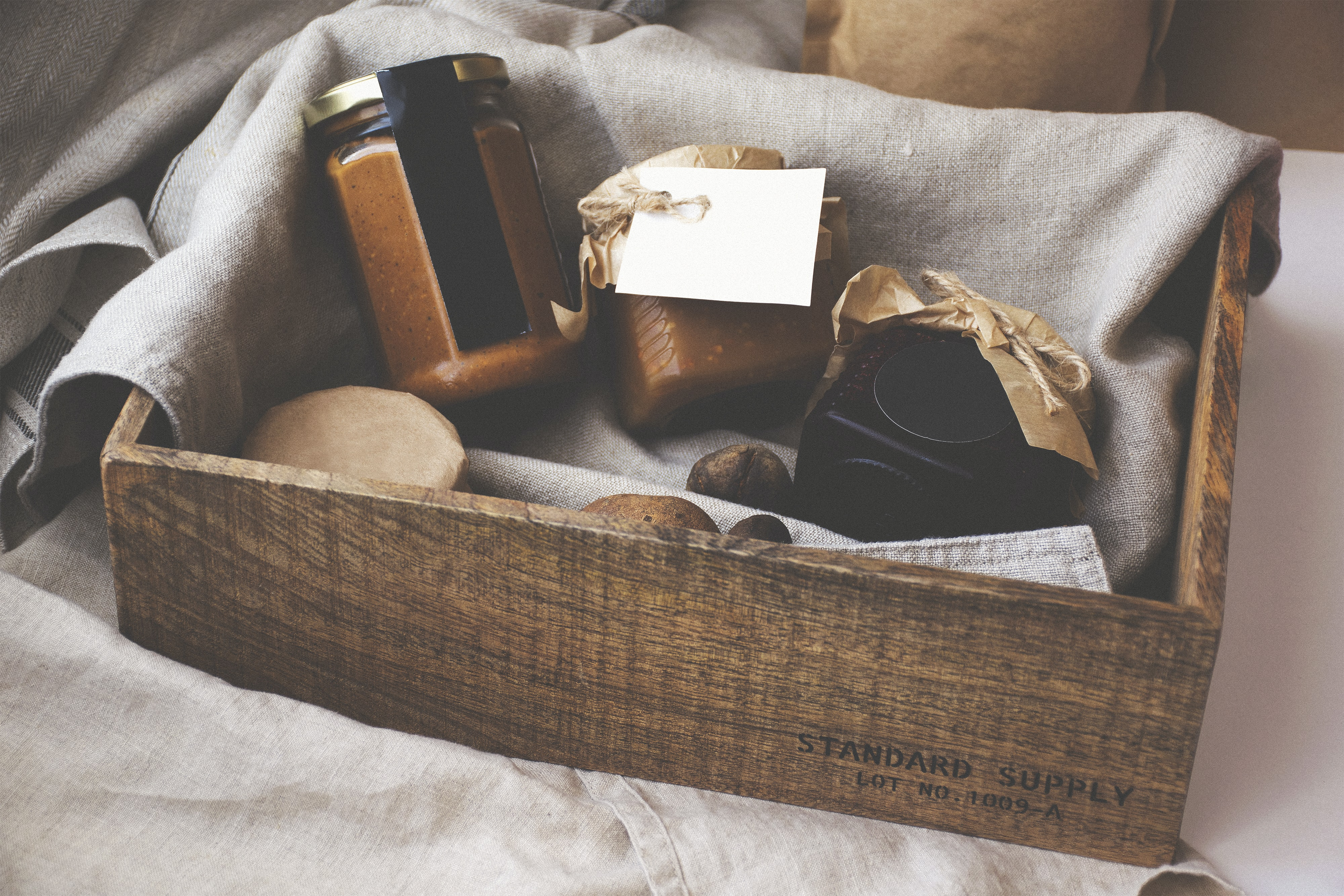A small wooden crate with preserves in jars