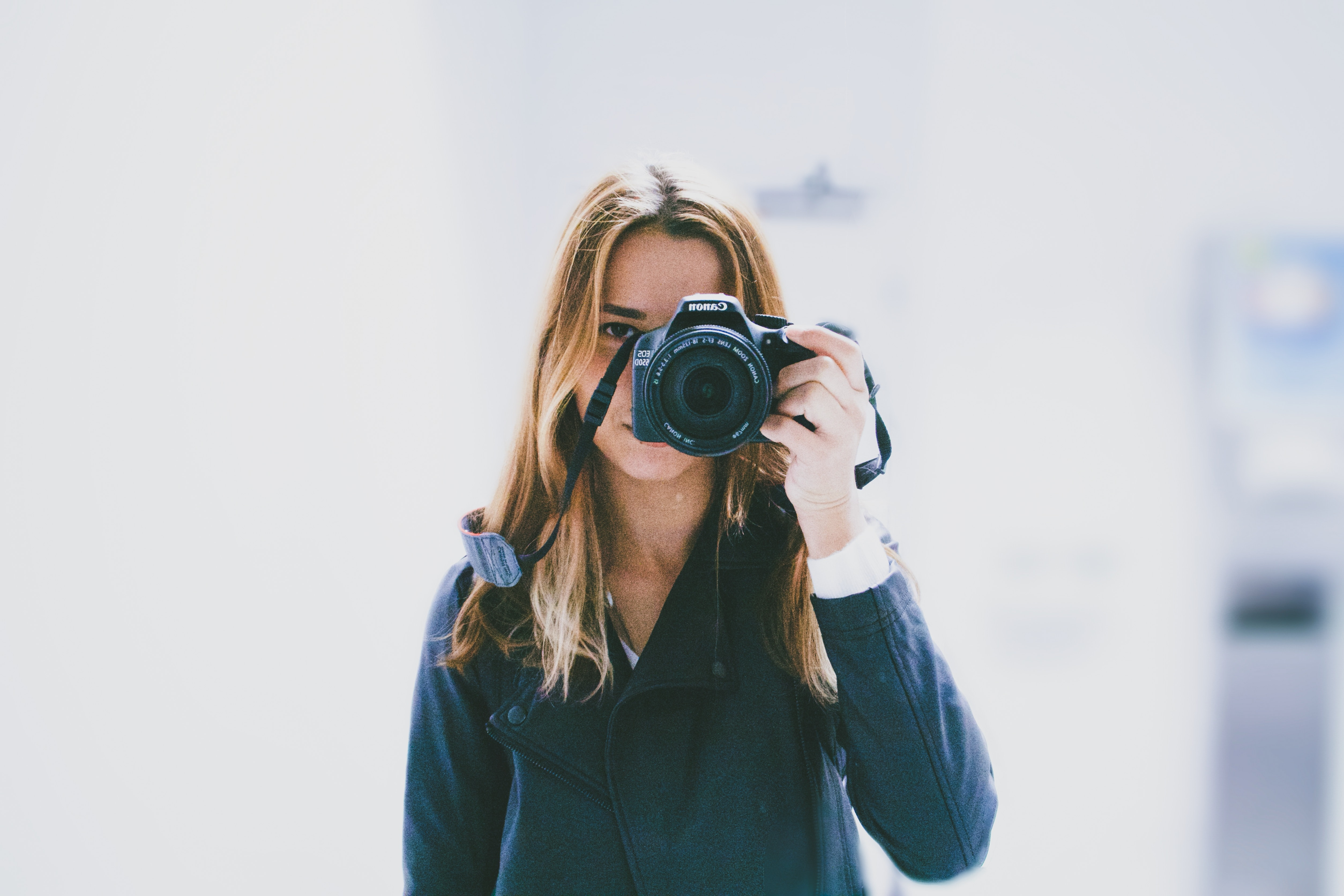 Photographer holding a camera over her face for a photo