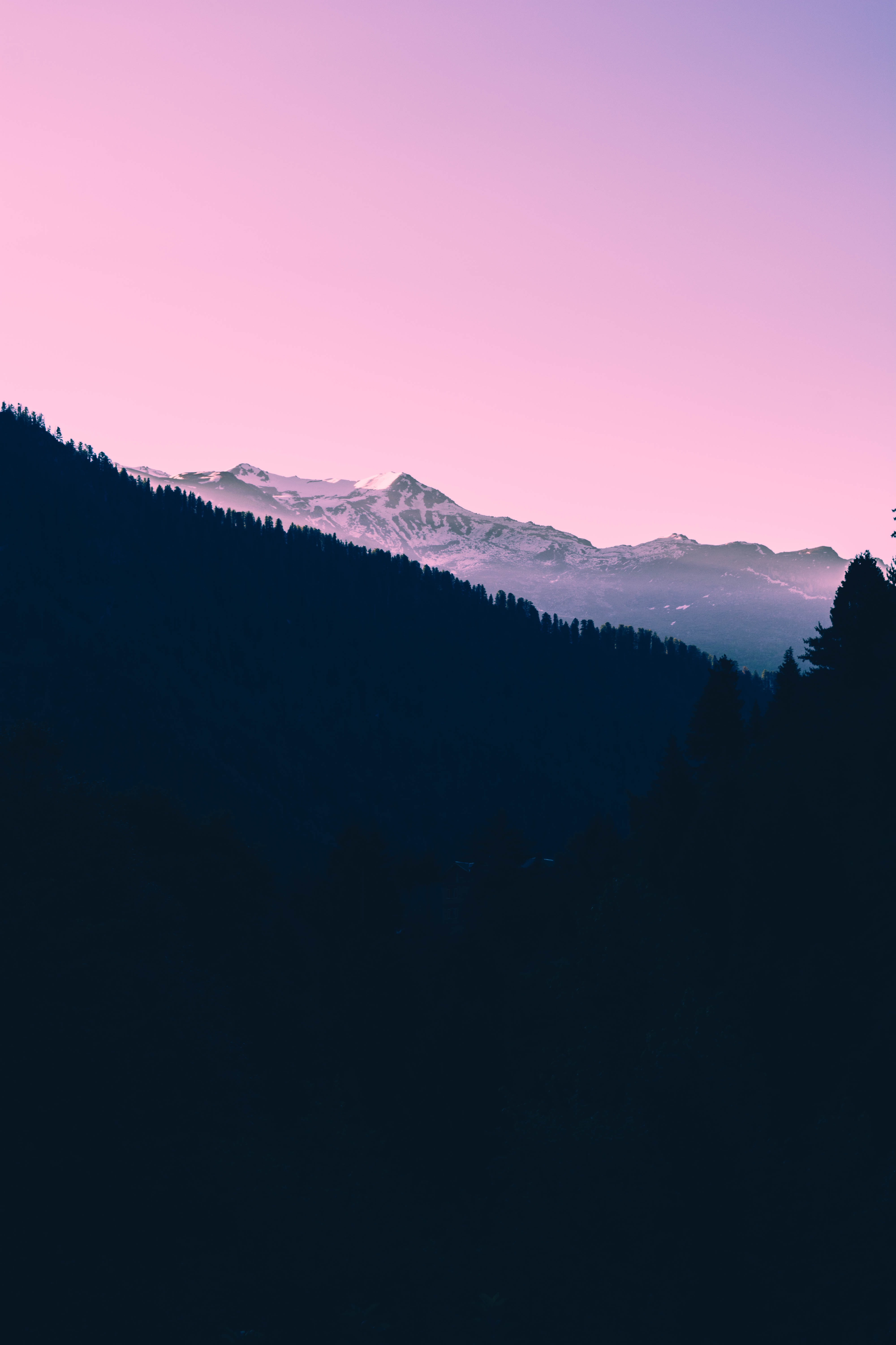 A dark sunset over snow covered mountains and a pink sky.