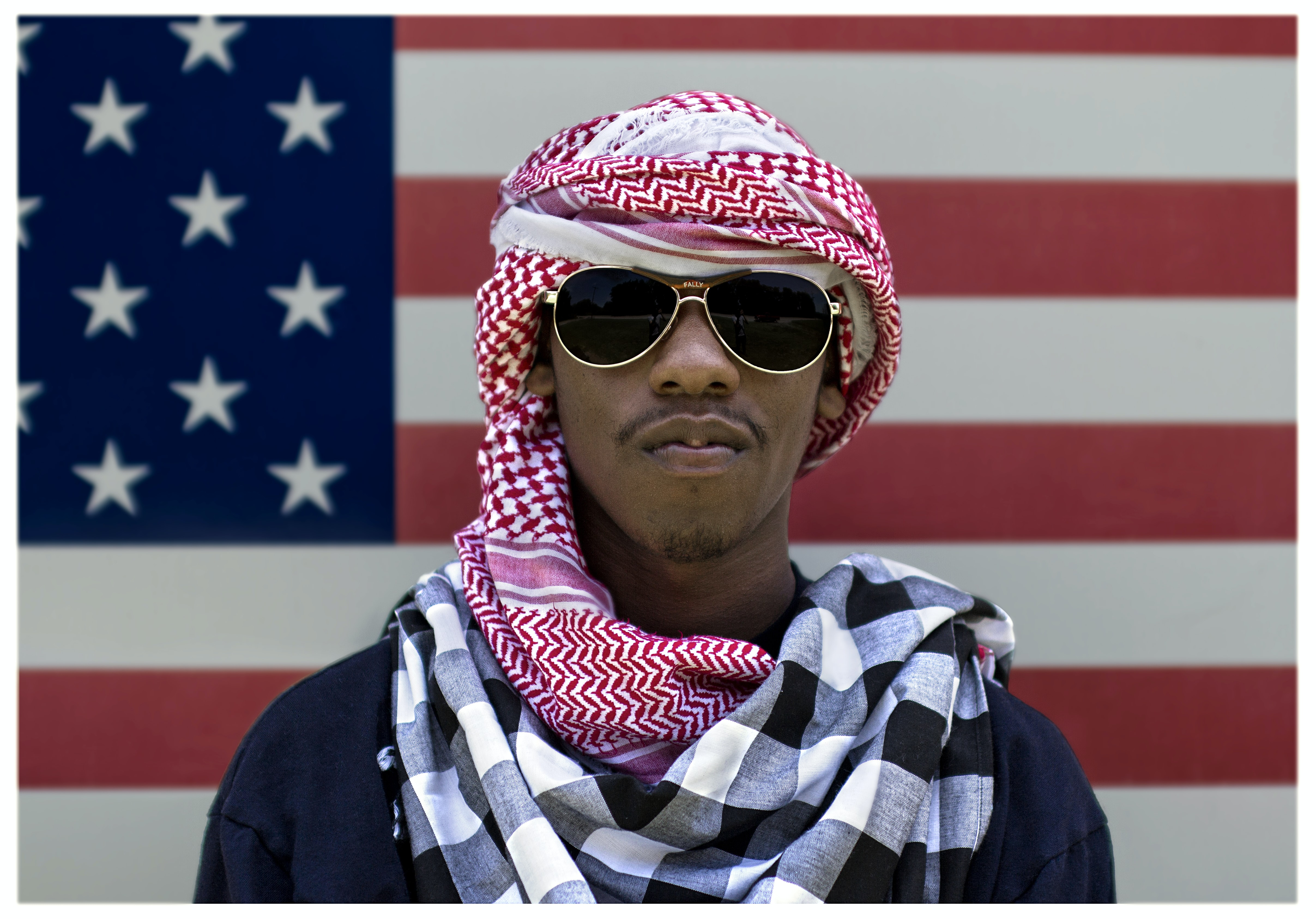 man wearing sunglasses in front of American flag