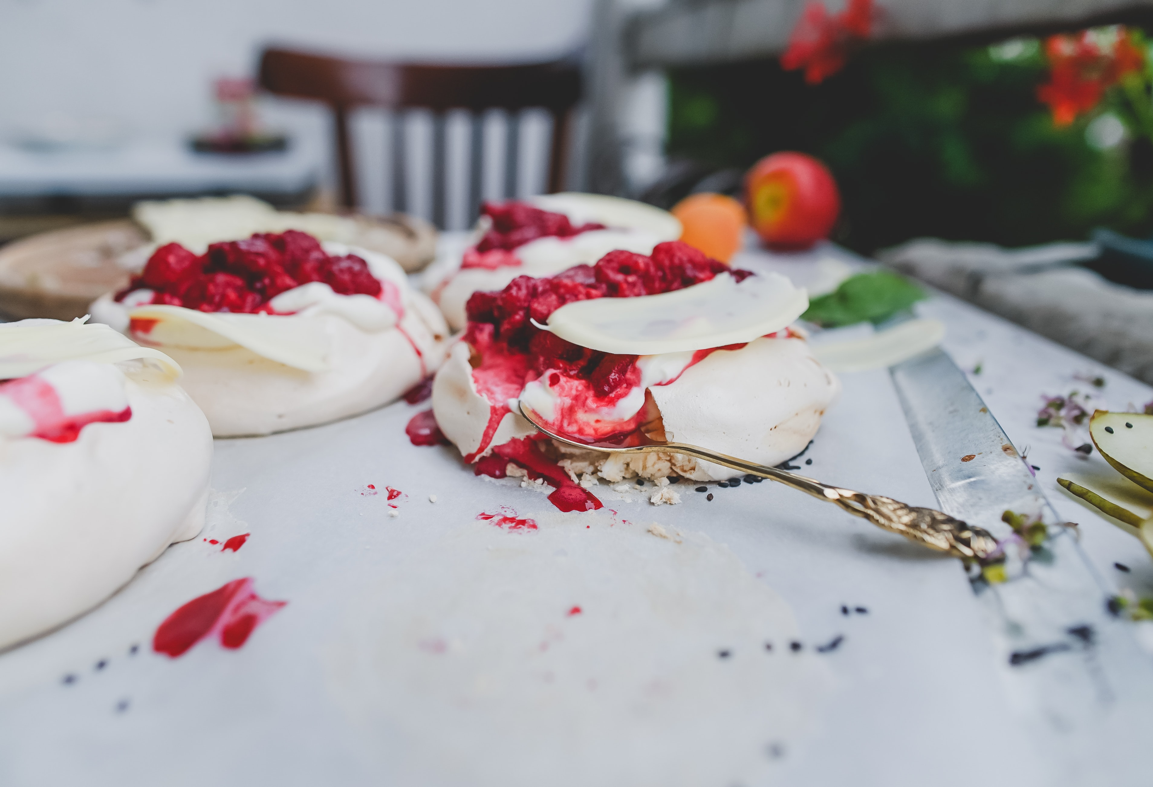Rustic tablescape with french meringue cakes with raspberry sauce for dessert