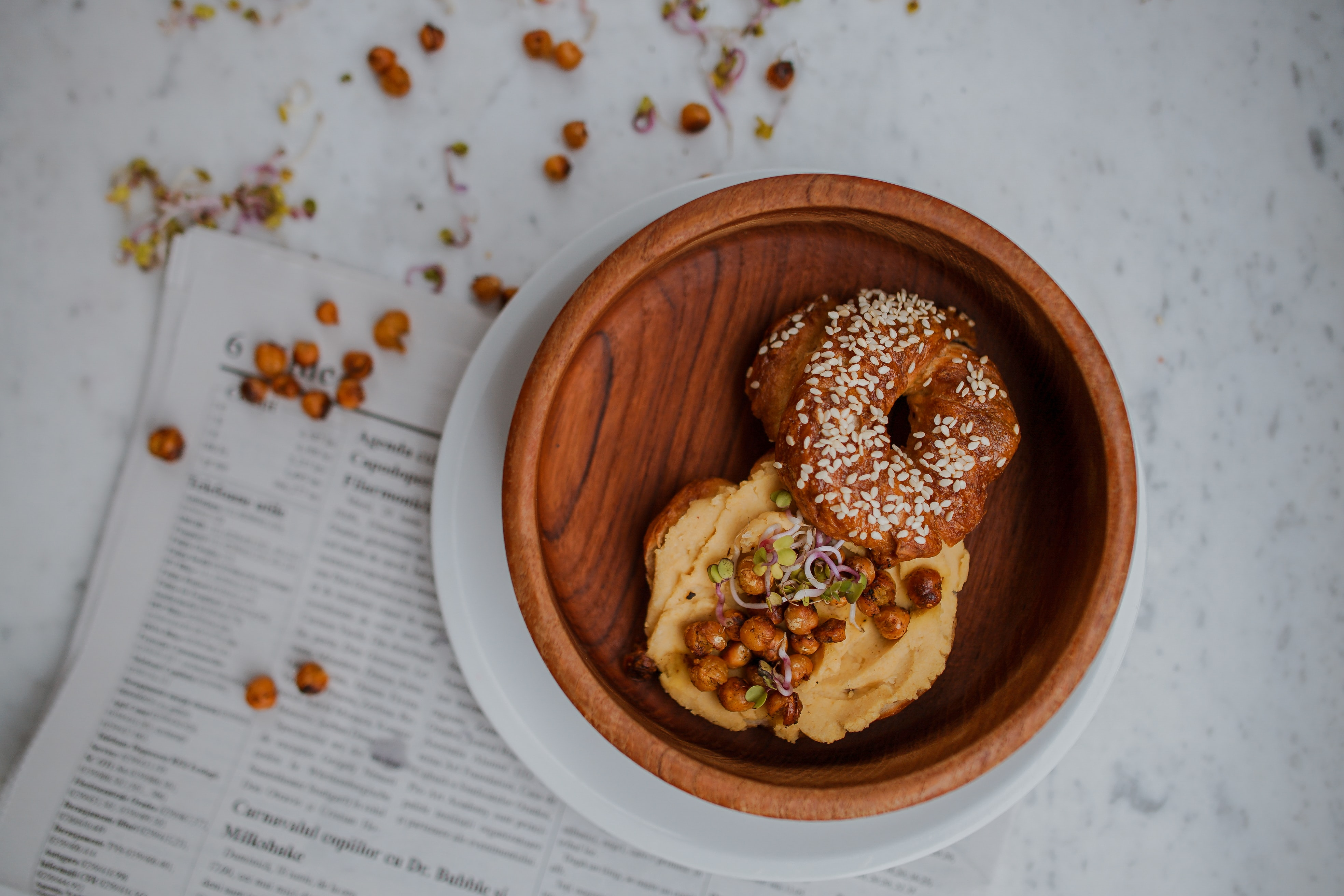 Bowl of bagel with hummus and roasted chickpeas on a Sunday newspaper