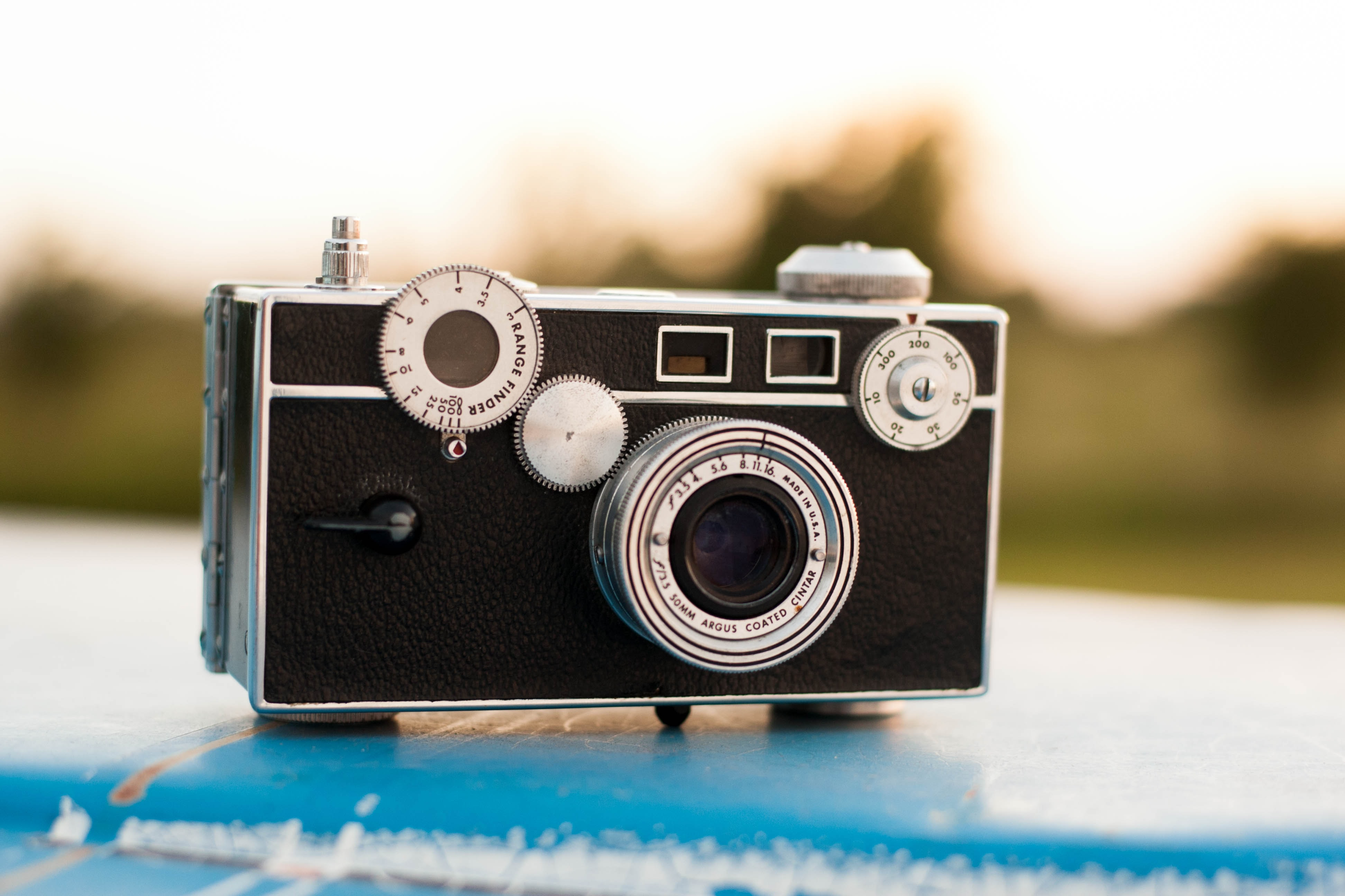 Vintage camera with a range finder and Argus Coated Cinter lens on a blue surface at dusk