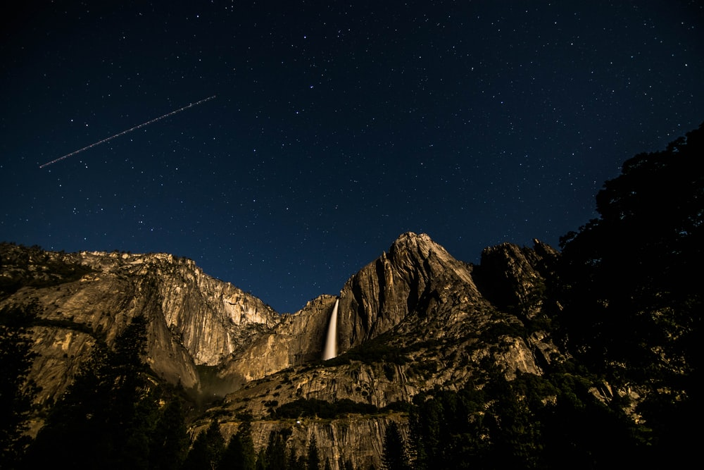 low angle photography of rock mountain under black sky at nighttime