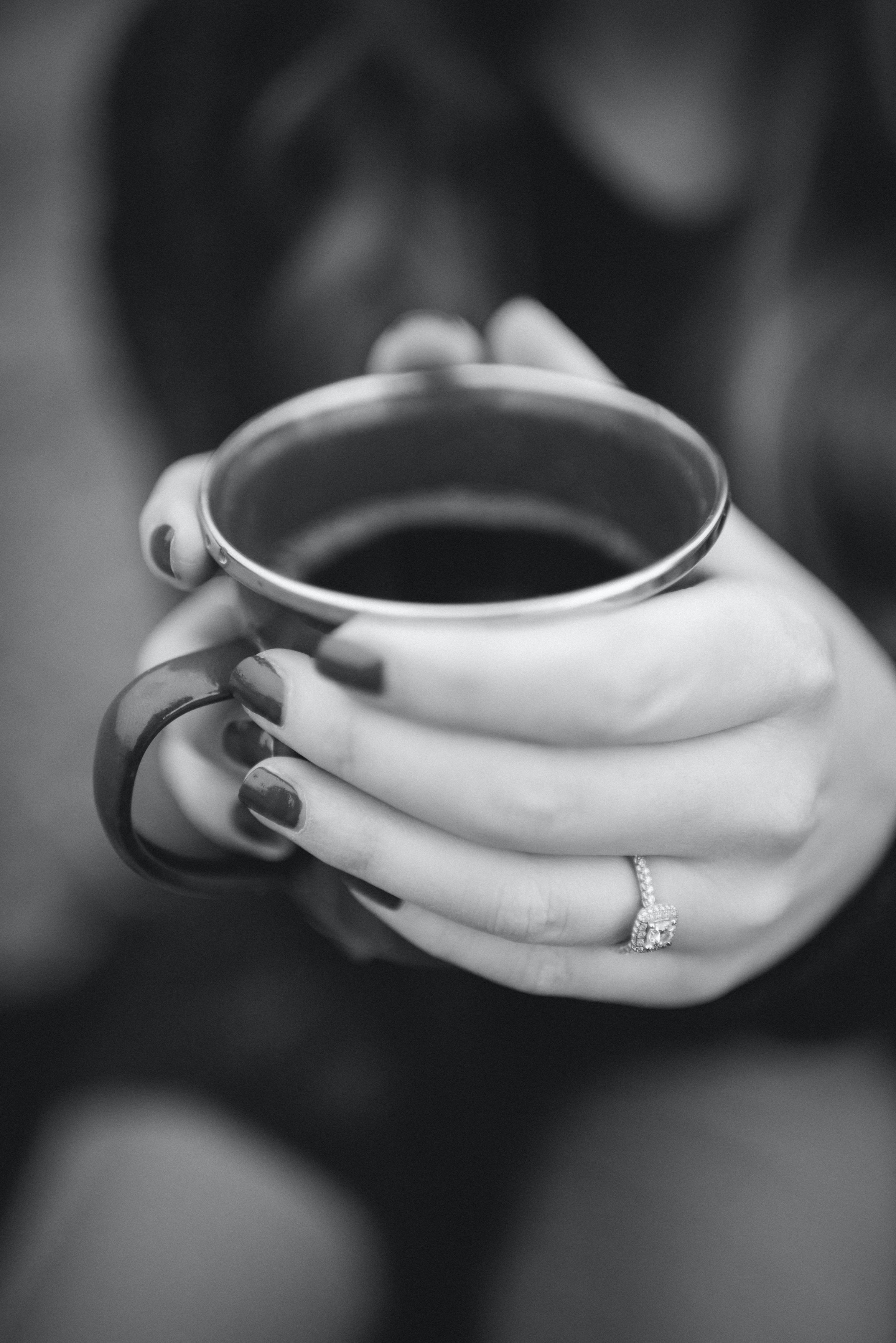 A black-and-white shot of a woman holding a cup of coffee