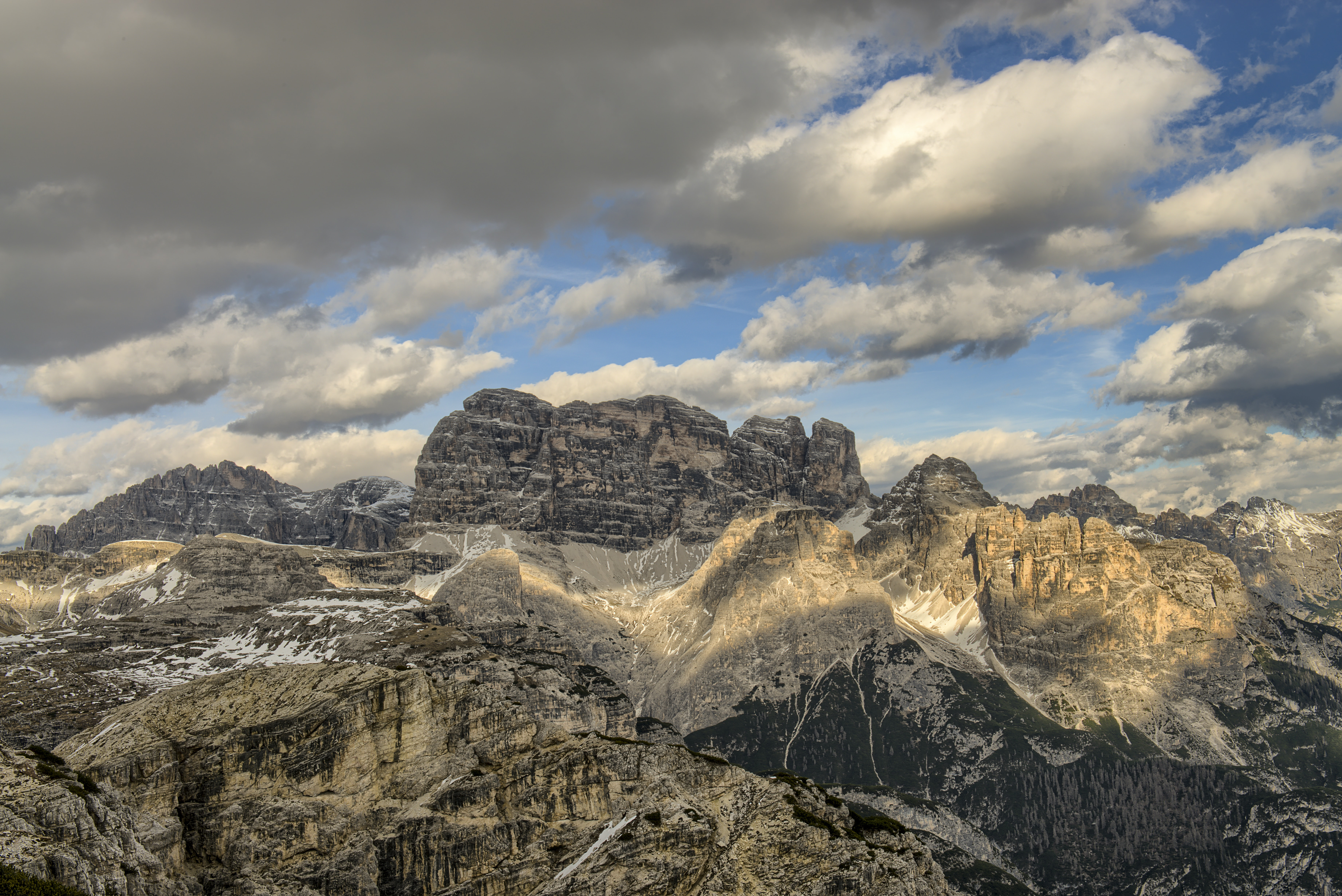 Tall rock towers in the Dolomites under a cloudy sky
