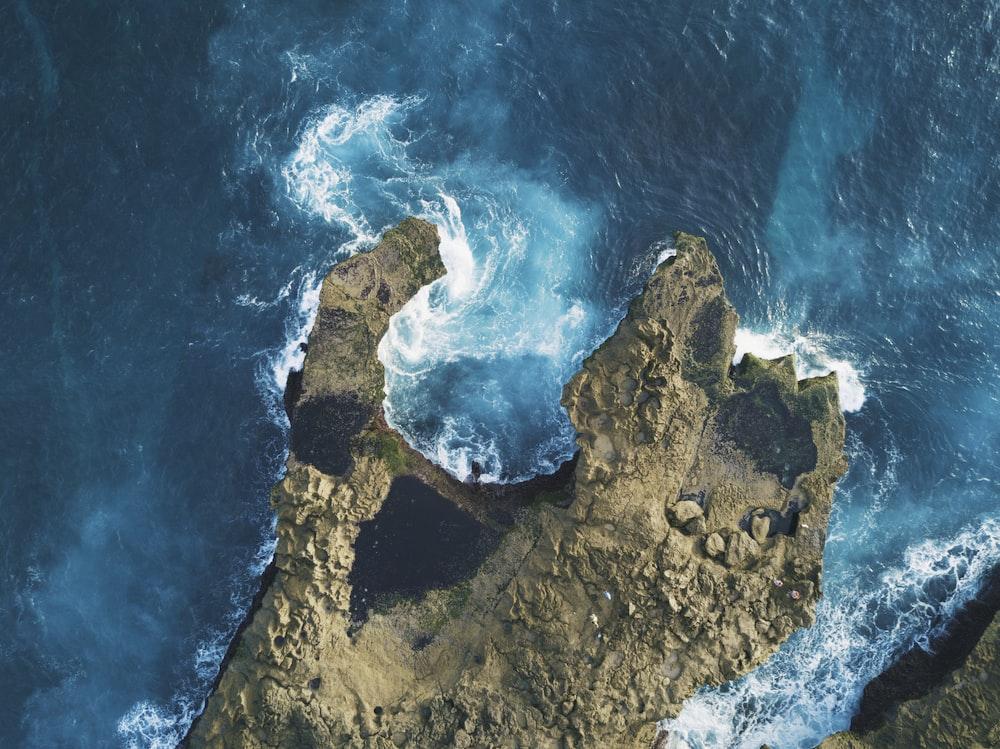 photo of brown rocks between blue body of water