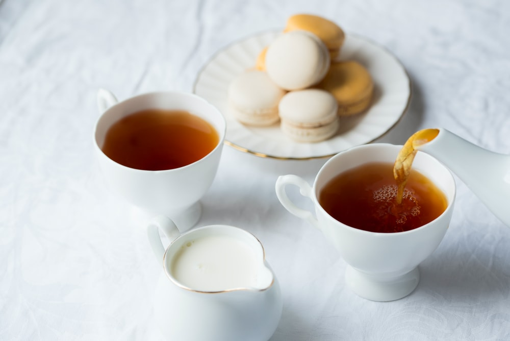 Two tea cups filled with tea and a plate of macaroons on a table
