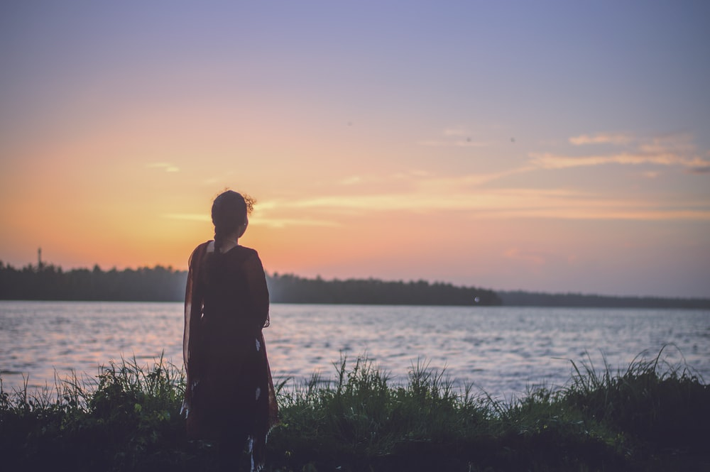silhouette photography of woman looking at body of water