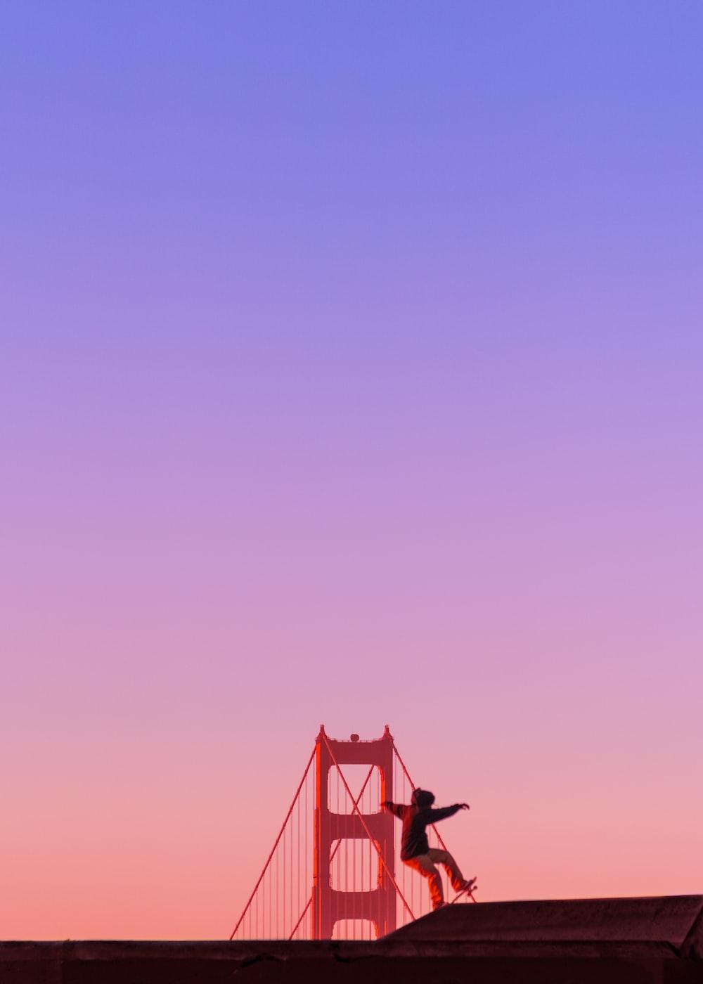 man riding on skateboard front of Golden Gate Bridge