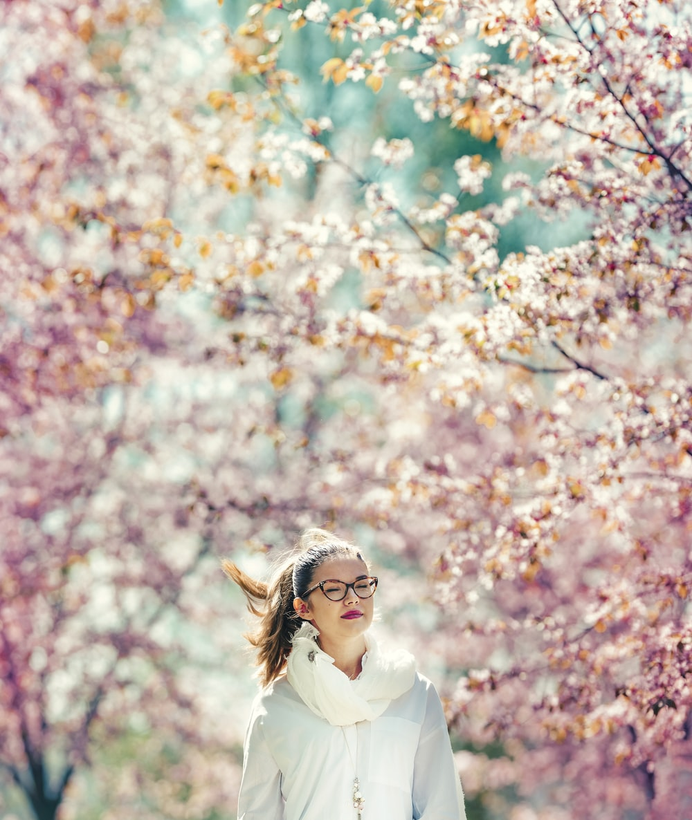 woman standing on pink cherry trees sorrounded area