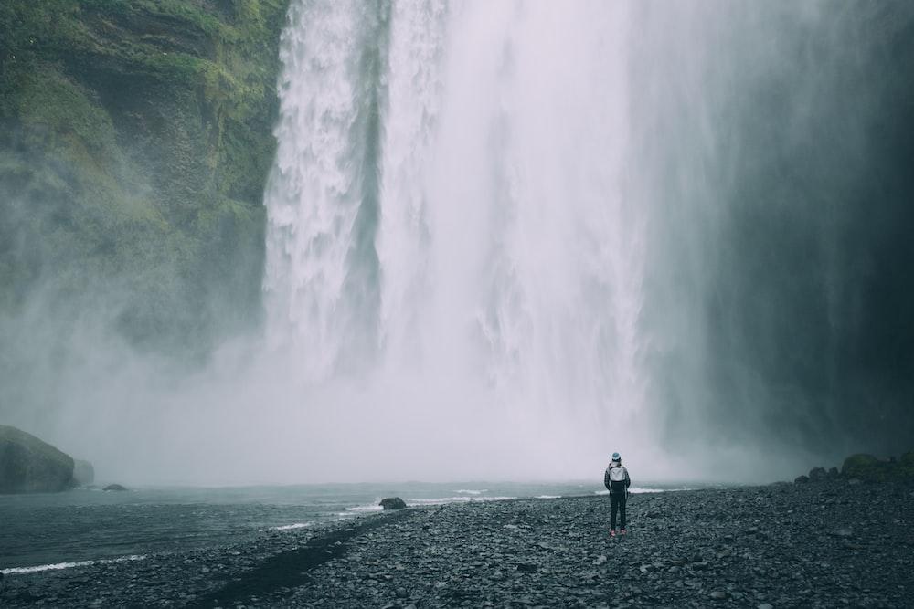 person standing near mountain falls