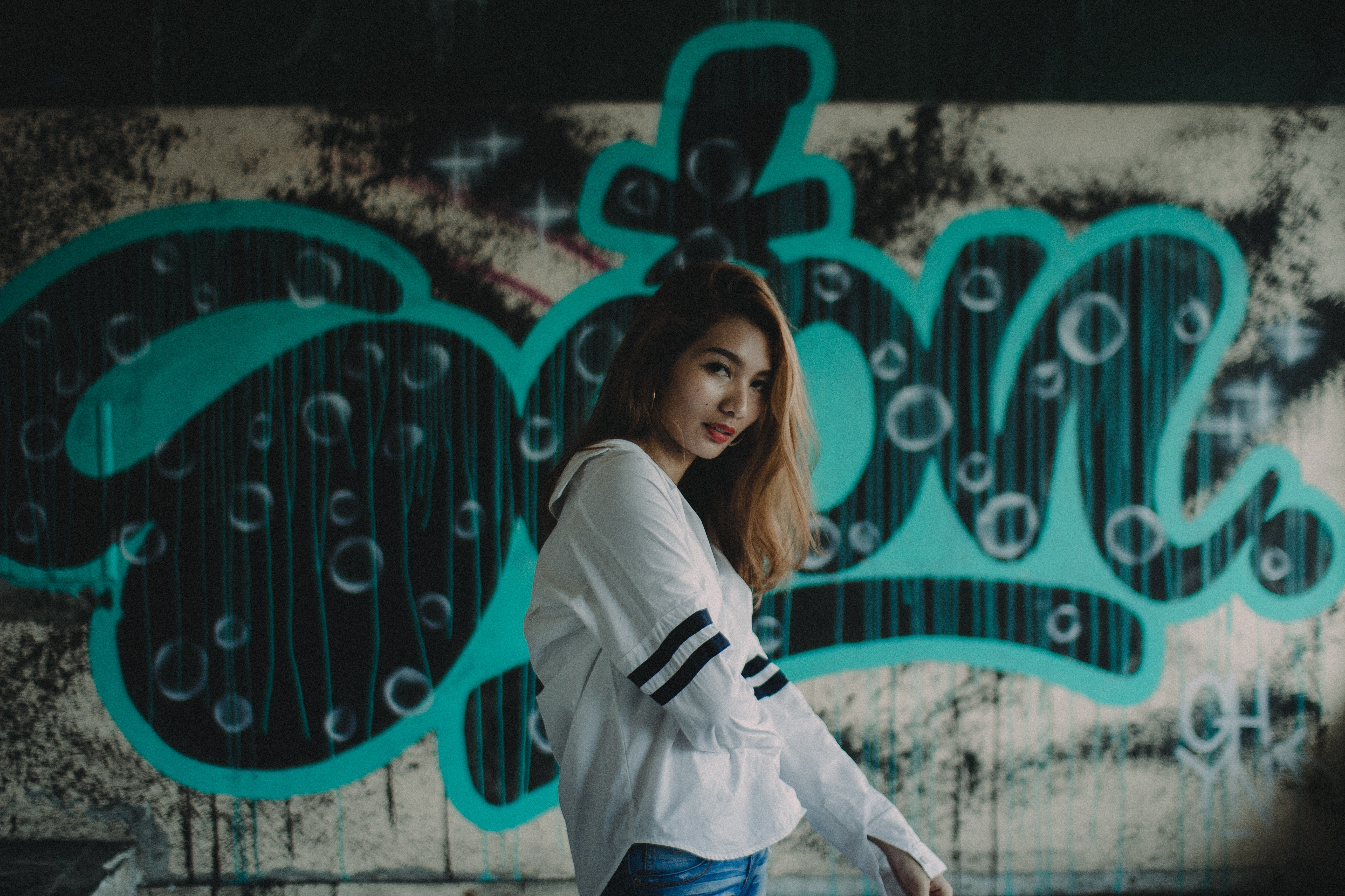 Woman in urban streetwear smiles subtly in front of a graffiti wall