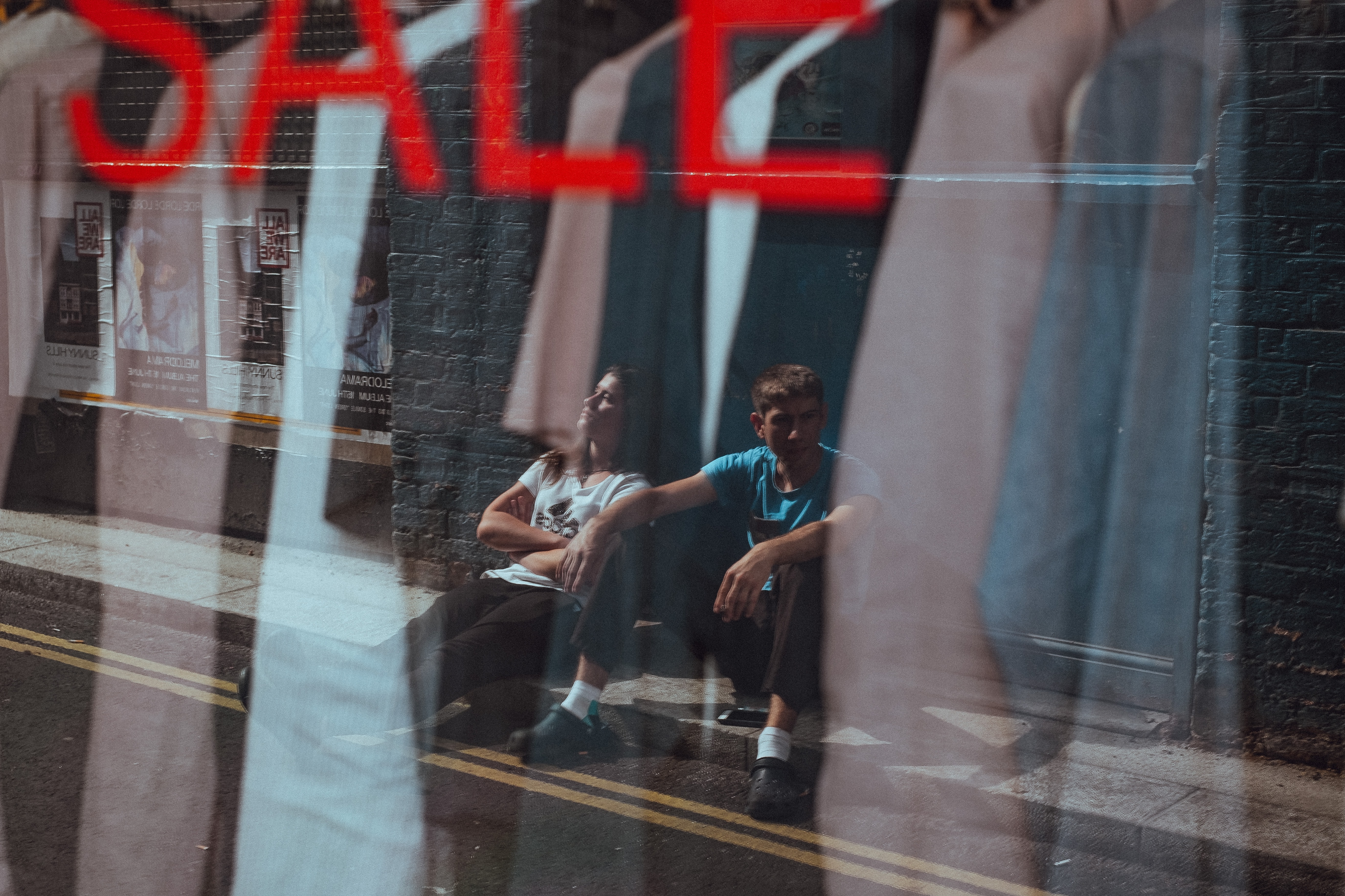 A man and woman sitting against a wall, reflected in a shop window