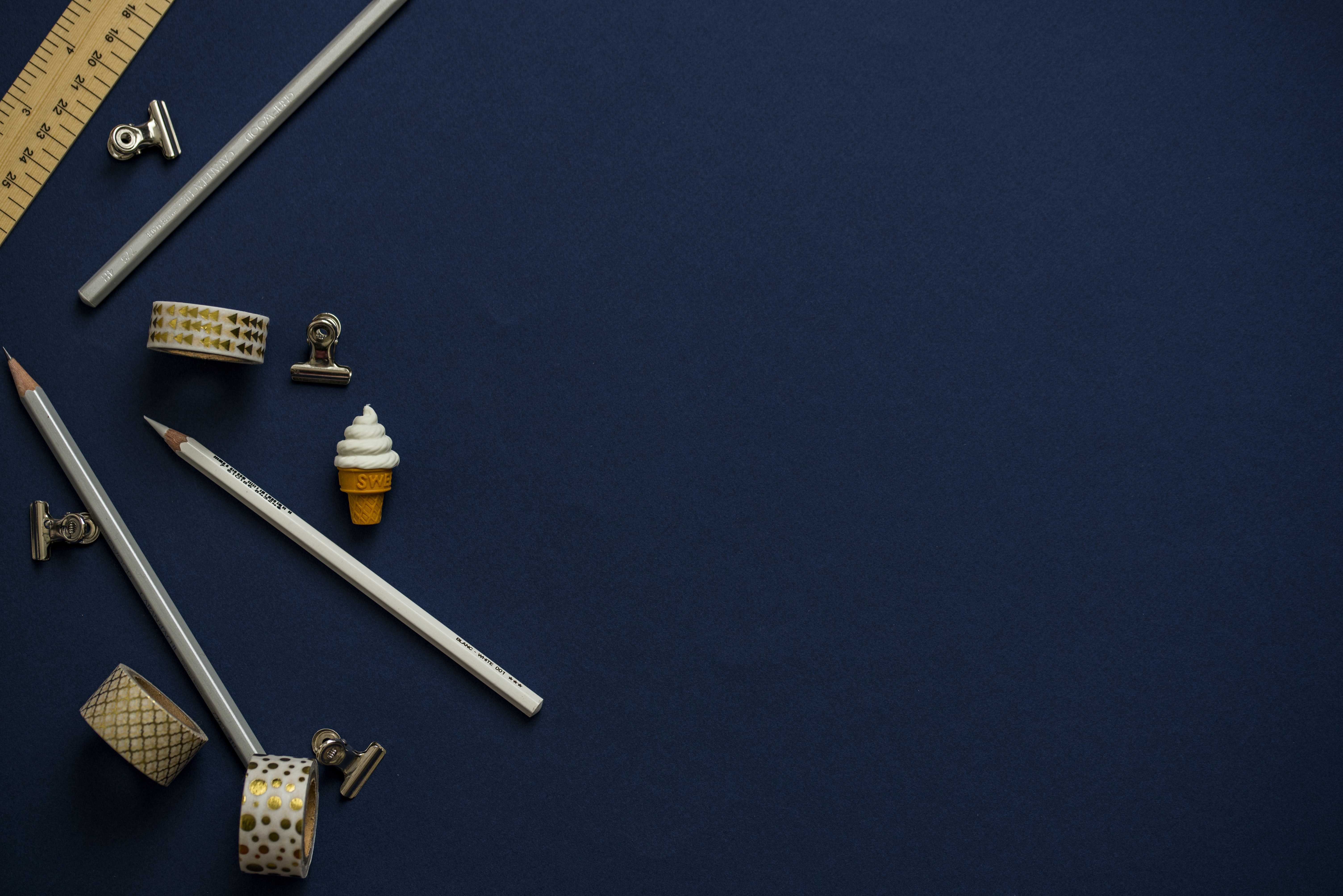 An overhead shot of pencils, a ruler, scotch tape and bulldog clips on a dark blue surface