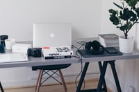 silver MacBook on top of table